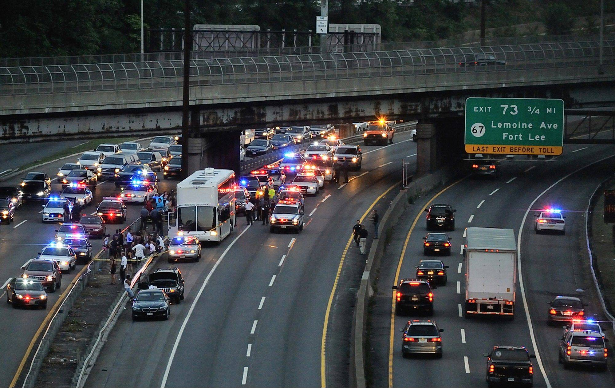In this Friday, Aug. 31, 2012 photo, emergency personnel work the scene where a teenager headed to a sweet 16 party was killed after he stuck his head out of the emergency hatch of a double-decker bus and hit the underside of a highway overpass, along Interstate 95, in Fort Lee, N.J.