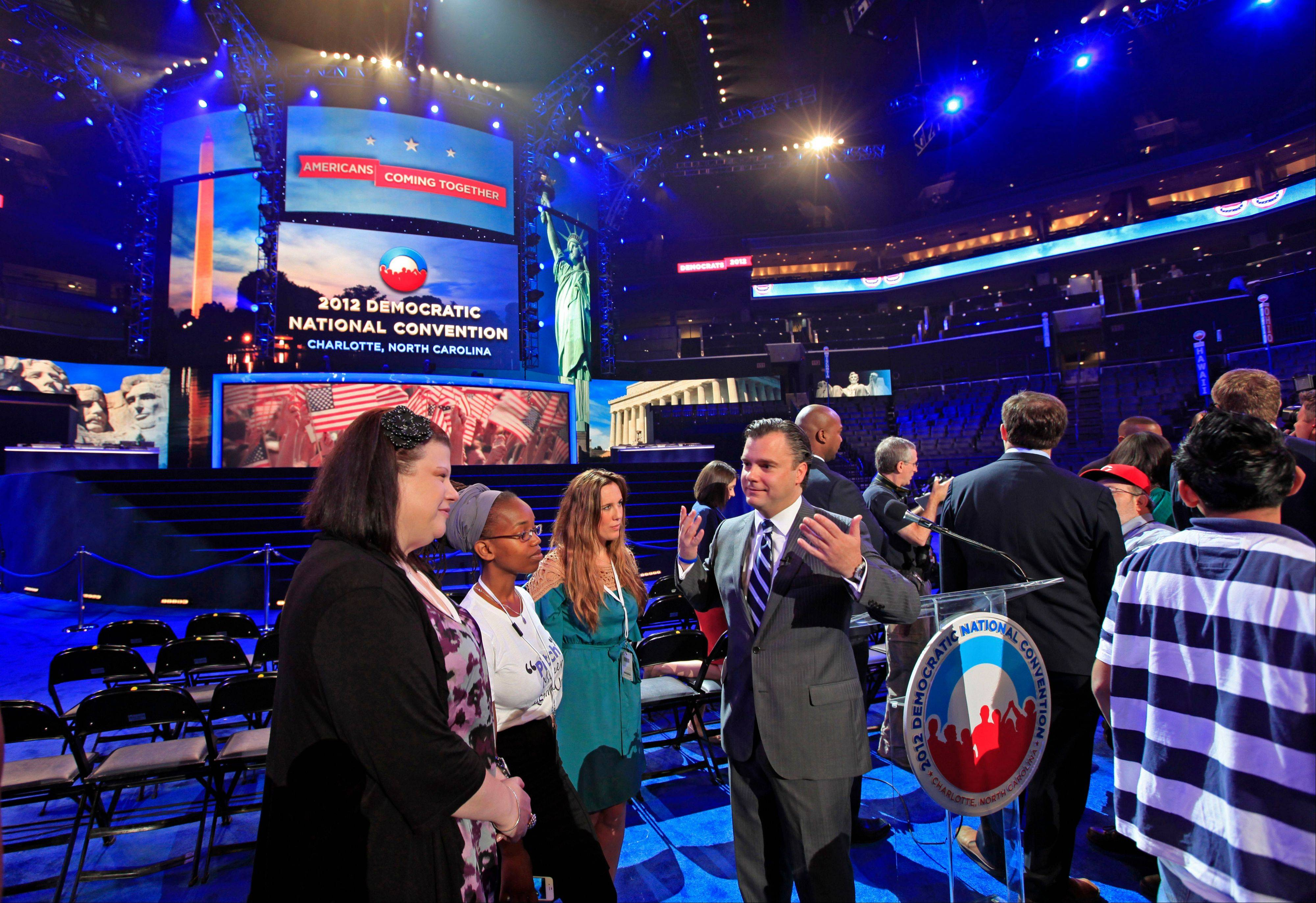 DNCC CEO Steve Kerrigan, center, talks with guests near the main stage during the public unveiling of Democratic National Convention's facilities at Time Warner Arena in Charlotte, N.C., Friday, Aug. 31, 2012.