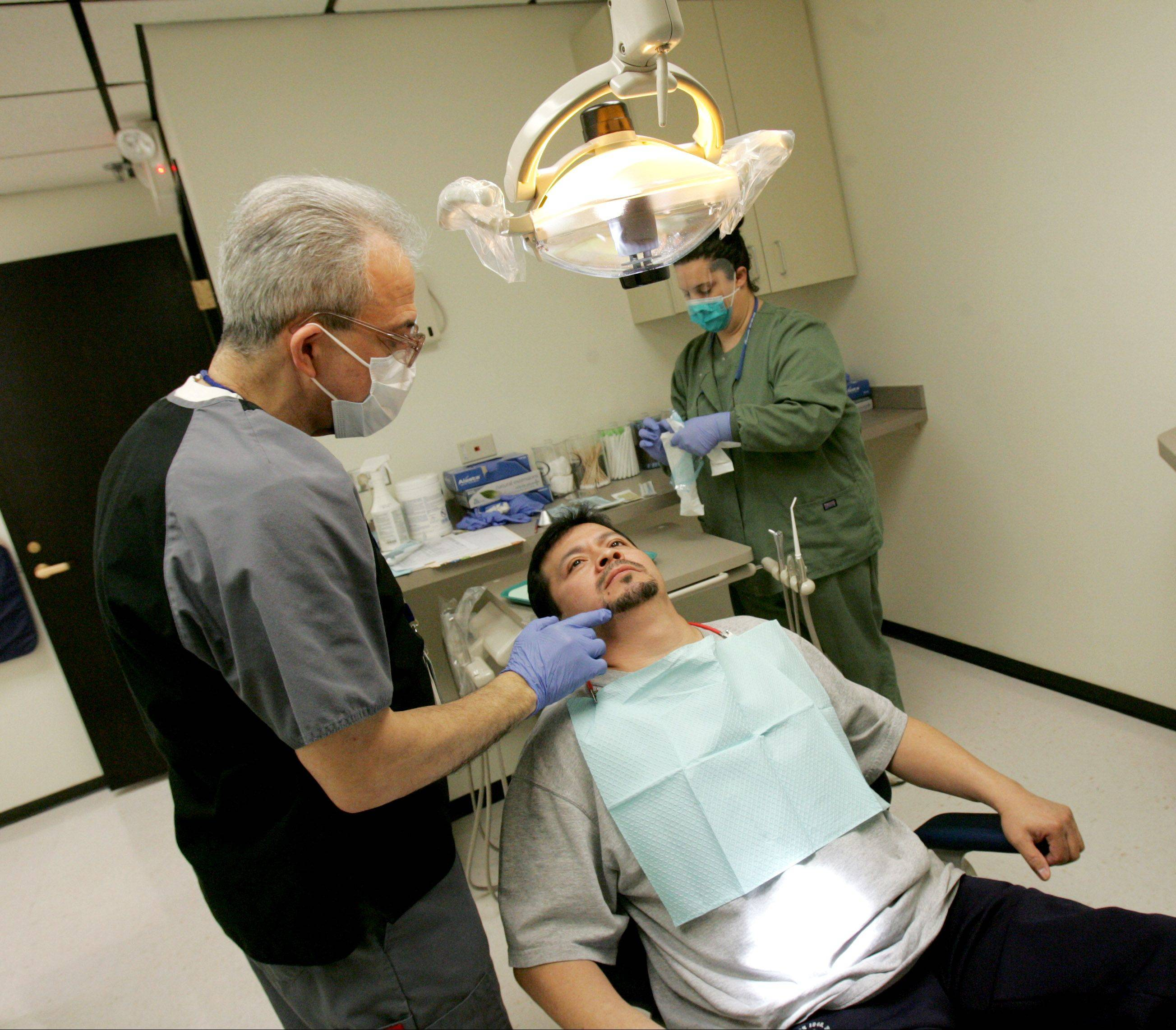 Leobardo Moralez of Bensenville is seen by Dr. John Ranieri, left, at the revamped urgent care dental clinic in the DuPage County Health Department building in Wheaton.