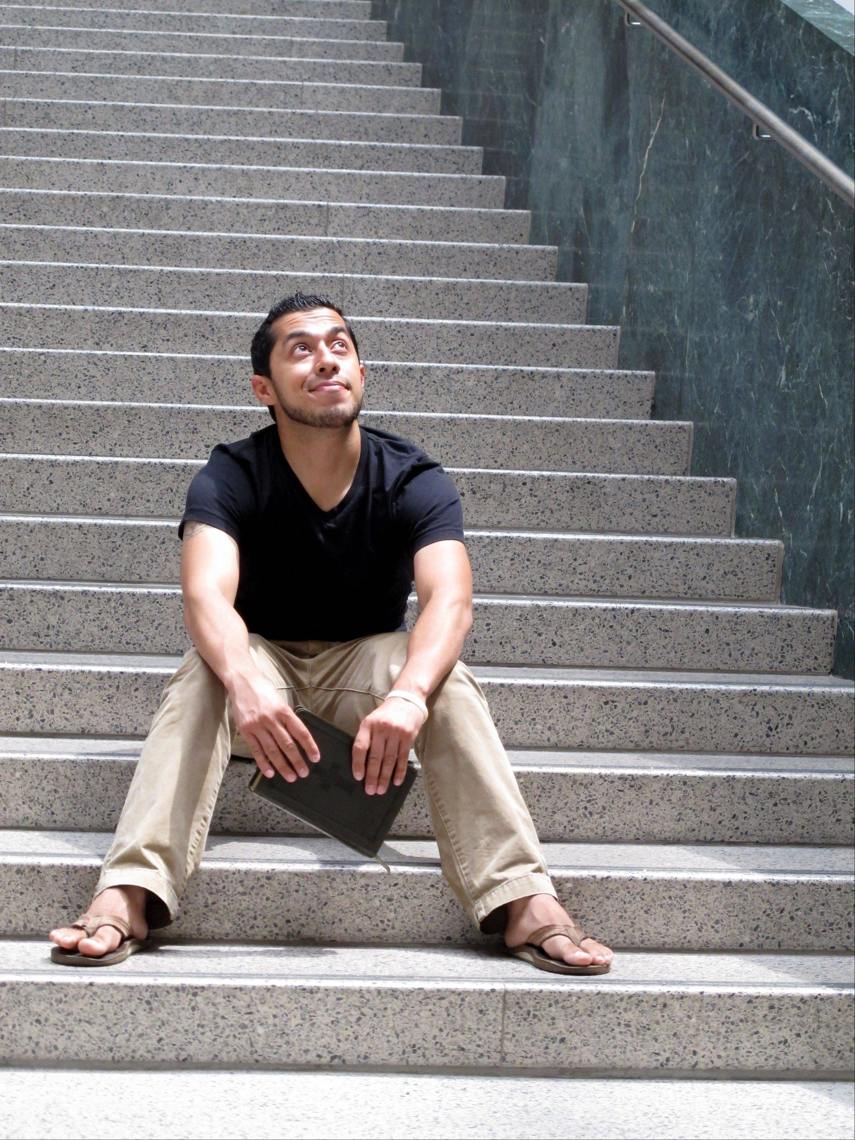 "Recent Ohio State University graduate Erik Santamaria sits on a campus library stairway in Columbus, Ohio. He's 30, between jobs, with $50,000 in student debt, and no clear sense what the future holds. But Erik Santamaria, Ohio-born son of Salvadorans, has a pretty awesome attitude about his country, his life and the world of possibilities. ""Maybe things won't work out the way I want,"" he offers. ""But, boy, I sure can't complain about how things have worked out so far."""