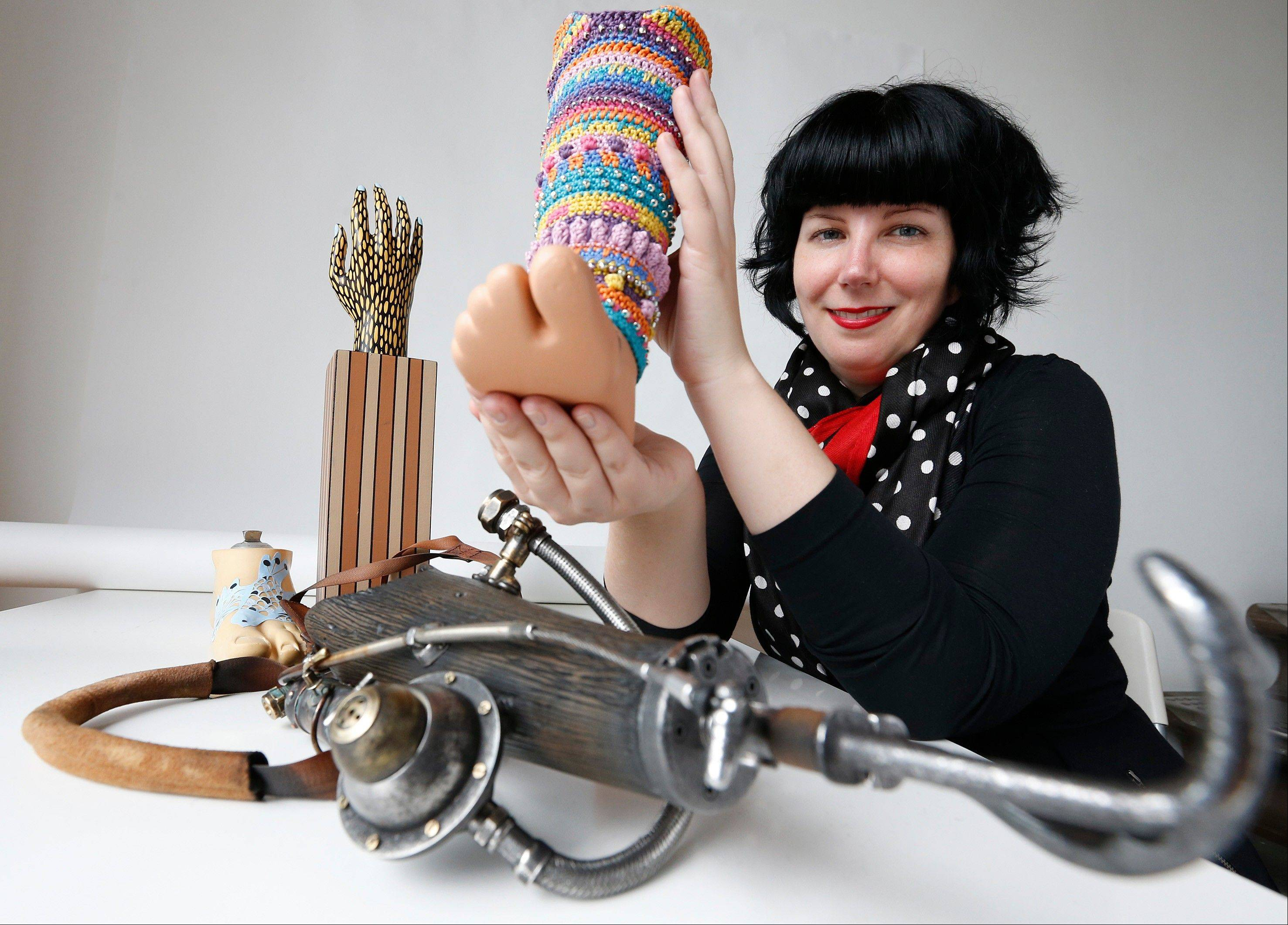 Priscilla Sutton, curator of the Spare Parts exhibition poses with some of the art work that has been all based on artists using prosthetic limbs that will be included in the show, at her home in London.