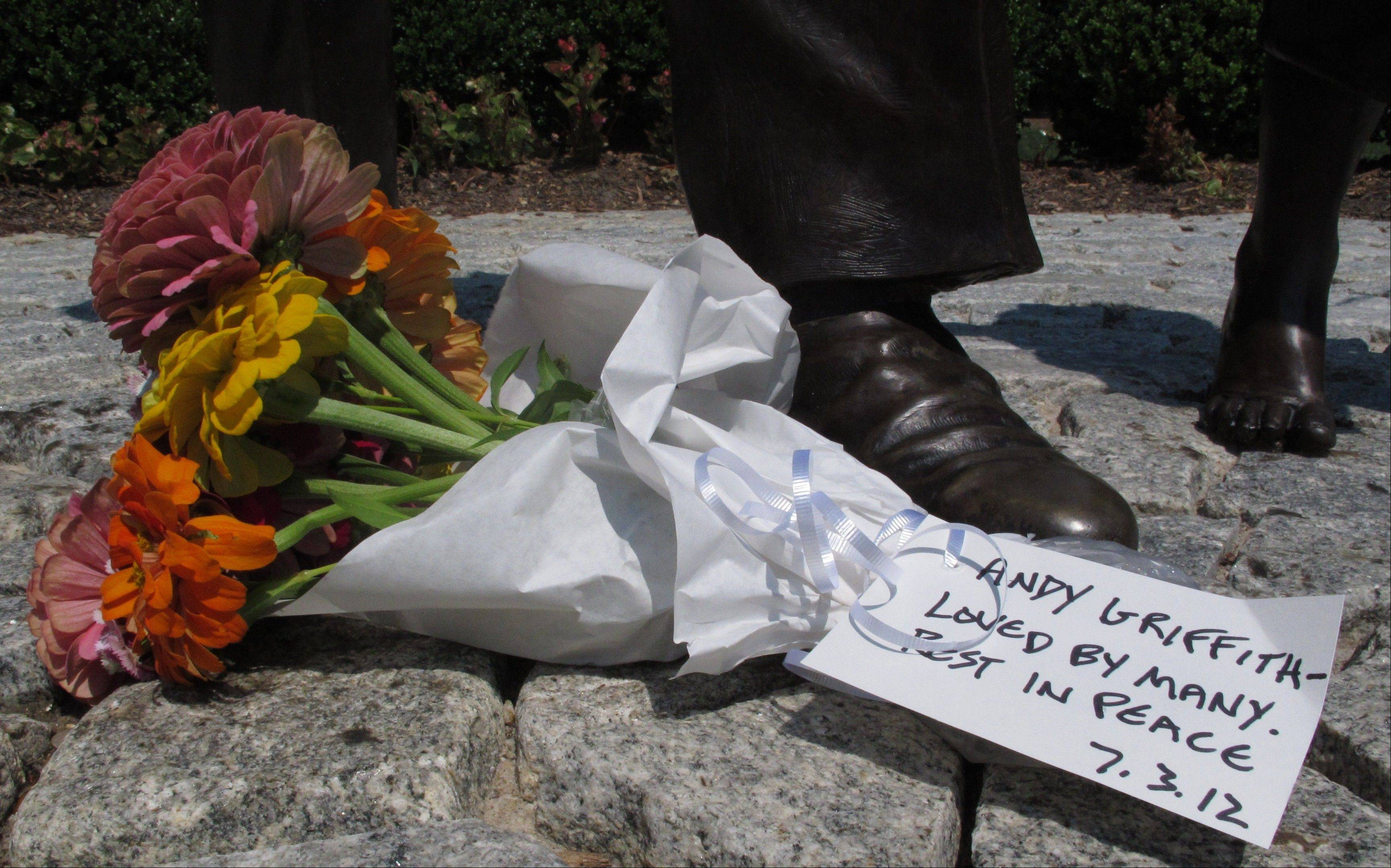 Well-wishers often place bouquets of flowers at the foot of a statue of Andy Griffith at Pullen Park in Raleigh, N.C.