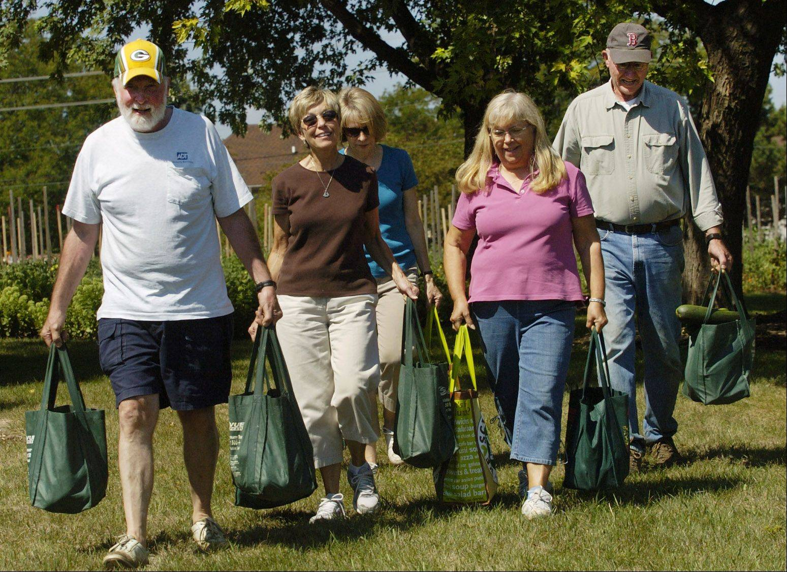 Tomato pickers from left, Richard Neidl, Nancy Erickson, Tina Lawrenz, Meta Anderson and Steven Larson carry their haul of tomatoes from the tomato garden behind Covenant Church in Schaumburg.