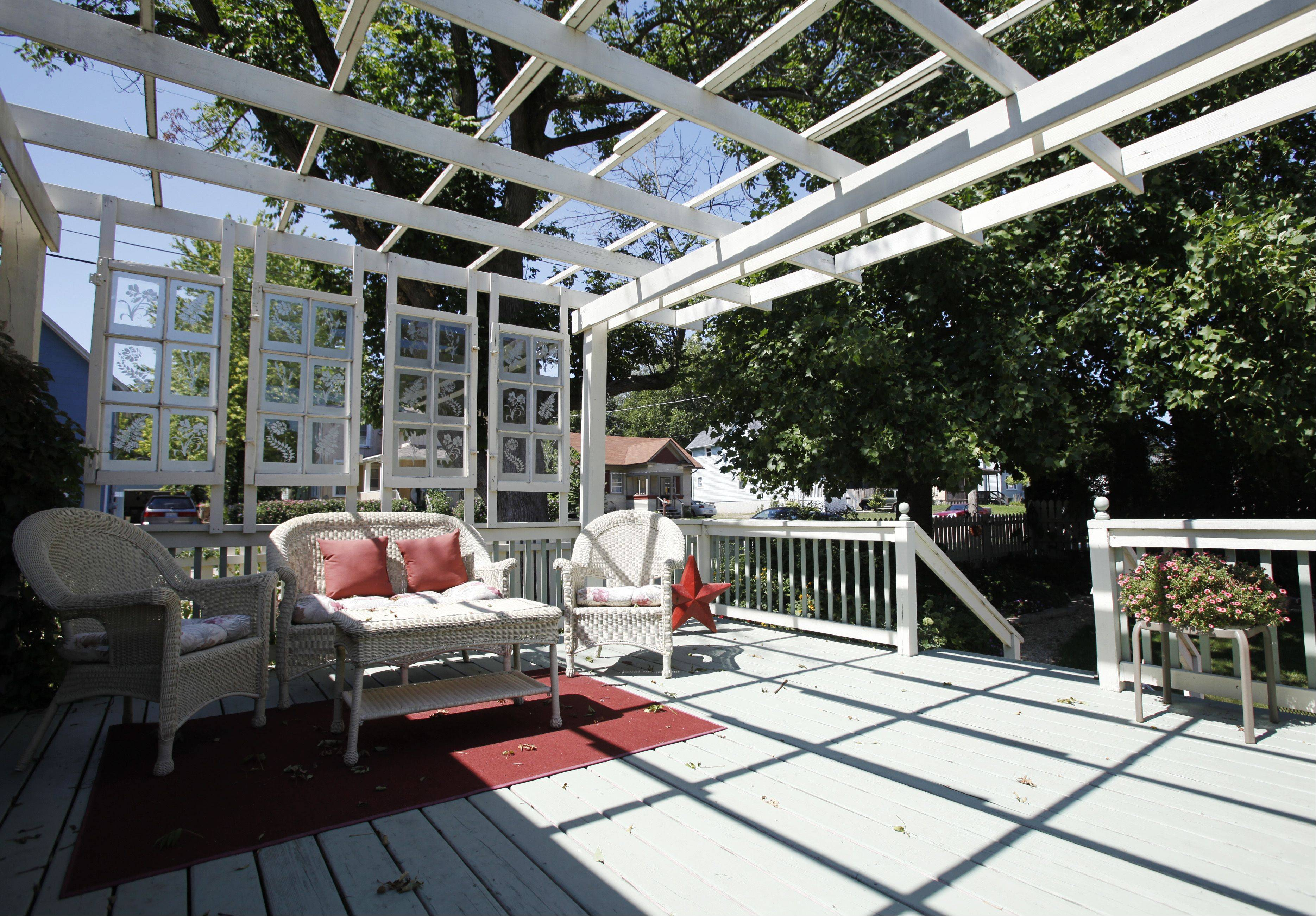 A large deck in the backyard, accented with hanging window frames and etched glass, is a focal point of relaxation at 670 Oak St. in Elgin.