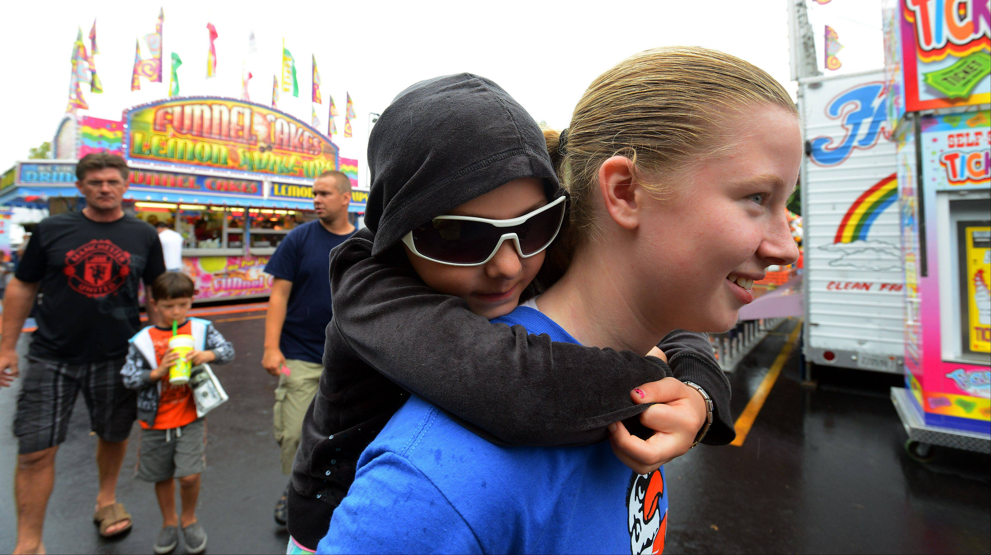Getting a ride in the rain from her sister, M.J. Morris, 6, holds on tight while Alexis, 14, does all the leg work as they venture around deciding what ride looks the coolest during the opening day of Septemberfest in Schaumburg on Saturday.