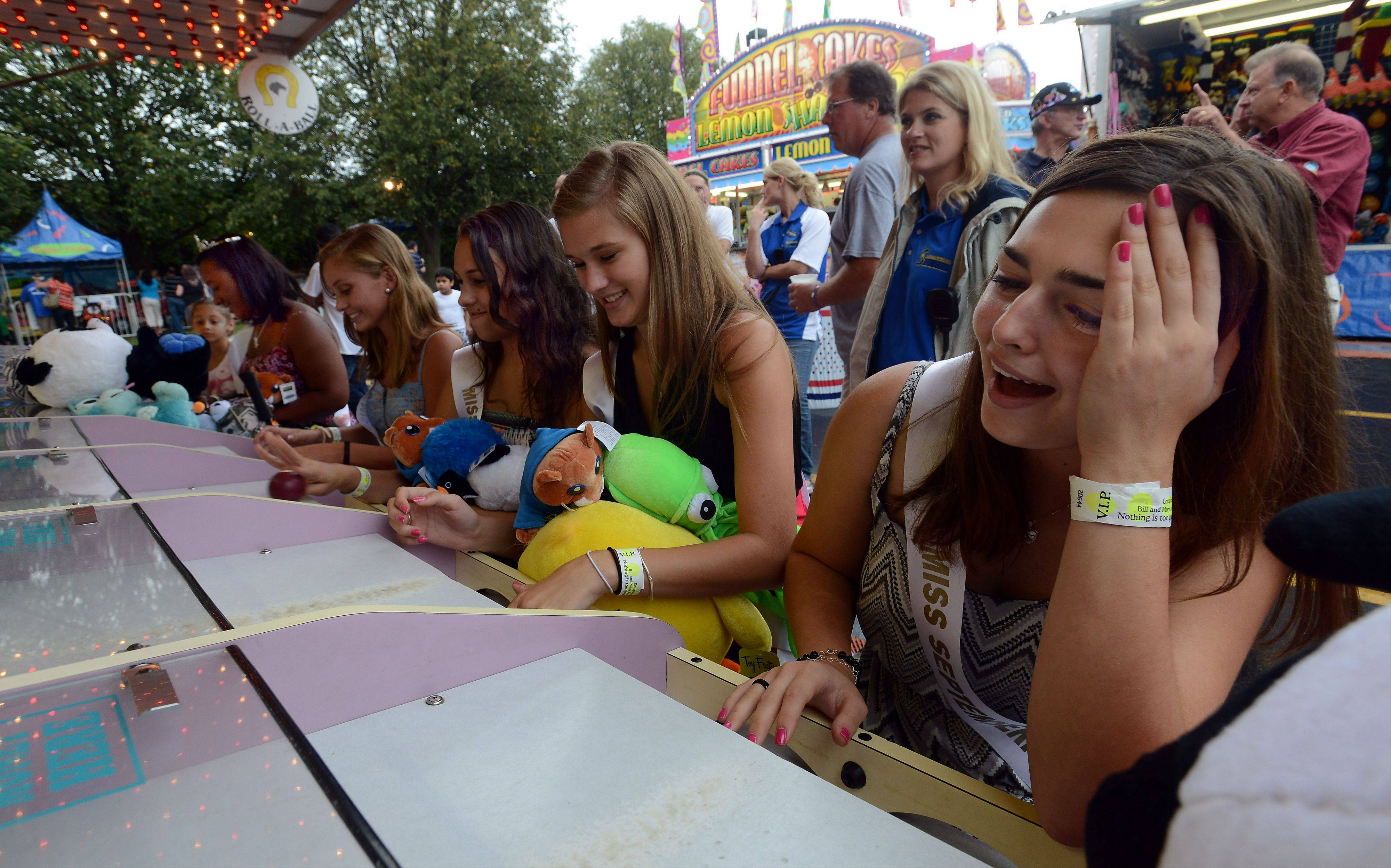Andreya De Larco, 17, of Schaumburg who sits on the Schaumburg queen court, plays one of the games at Septemberfest reacting to a not-so-great score on Saturday. The fest continues through Monday.