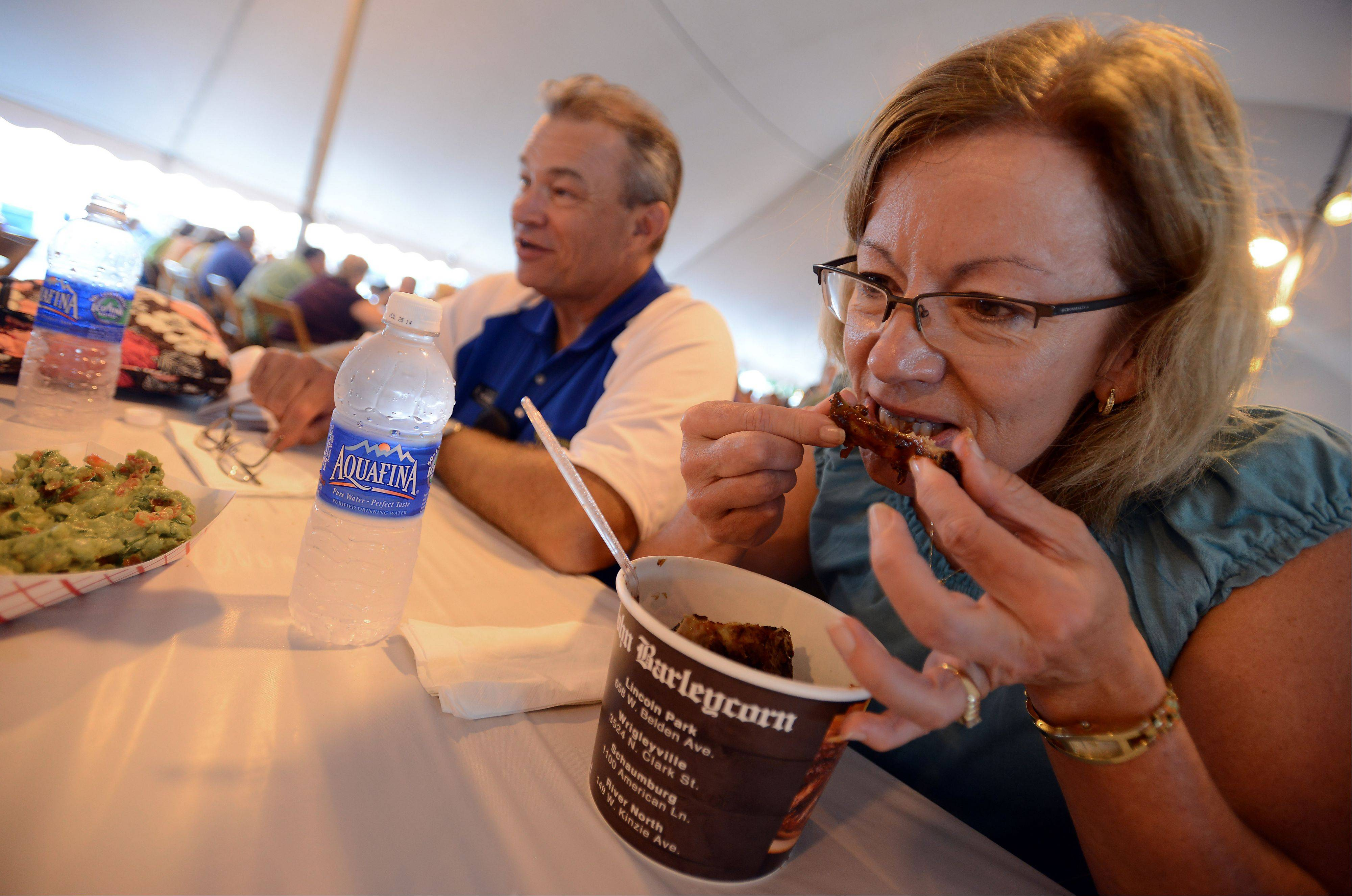 Staying out of the rain and enjoying some messy ribs is Nancy Rogers of Schaumburg.