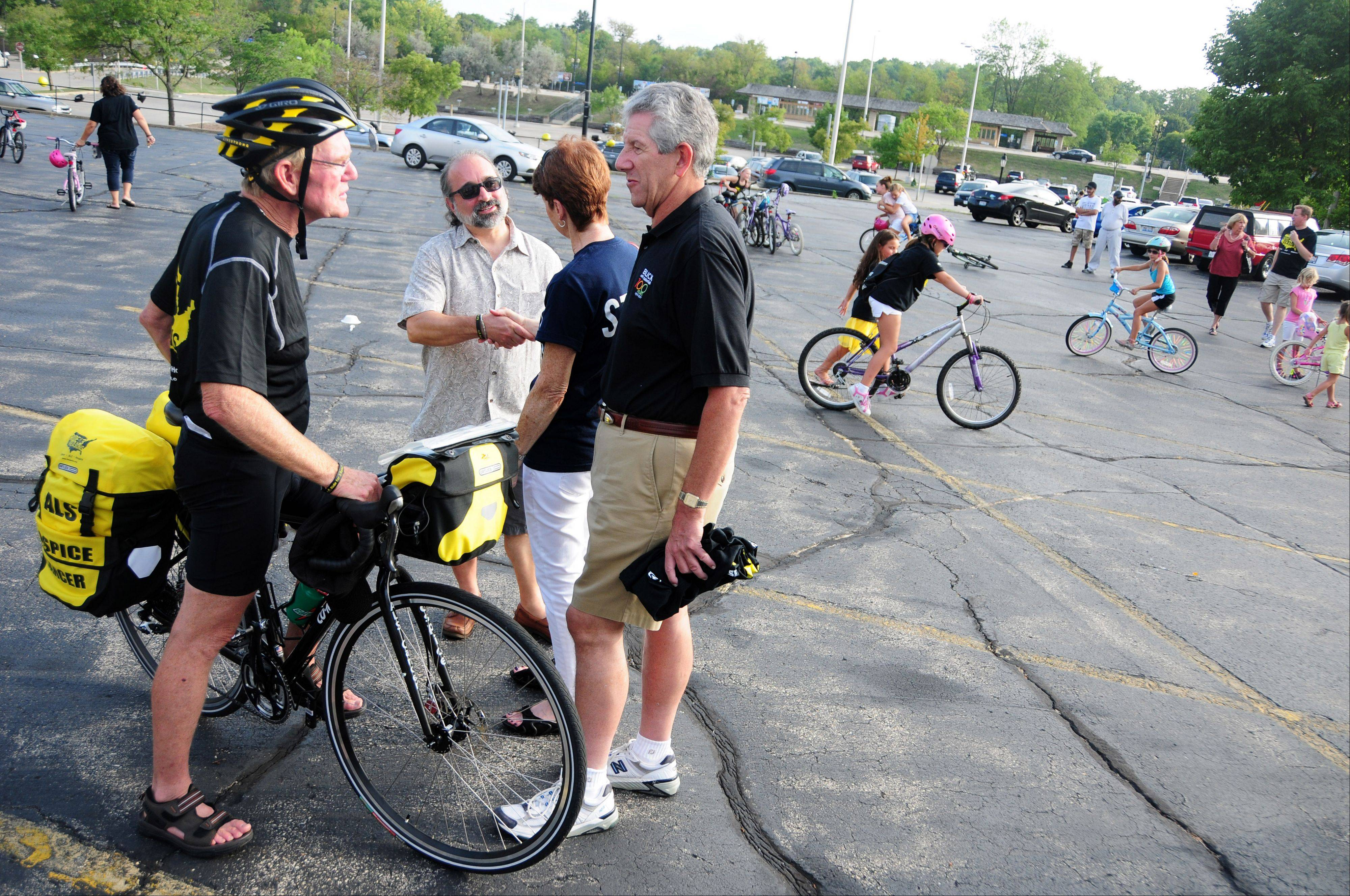 Barrington resident Bob Lee, 70, chats with friends while kids ride around the parking lot Sunday before embarking on the a bike ride around the perimeter of the United States to raise money for cancer research, ALS (Lou Gehrig's disease), and hospice education.