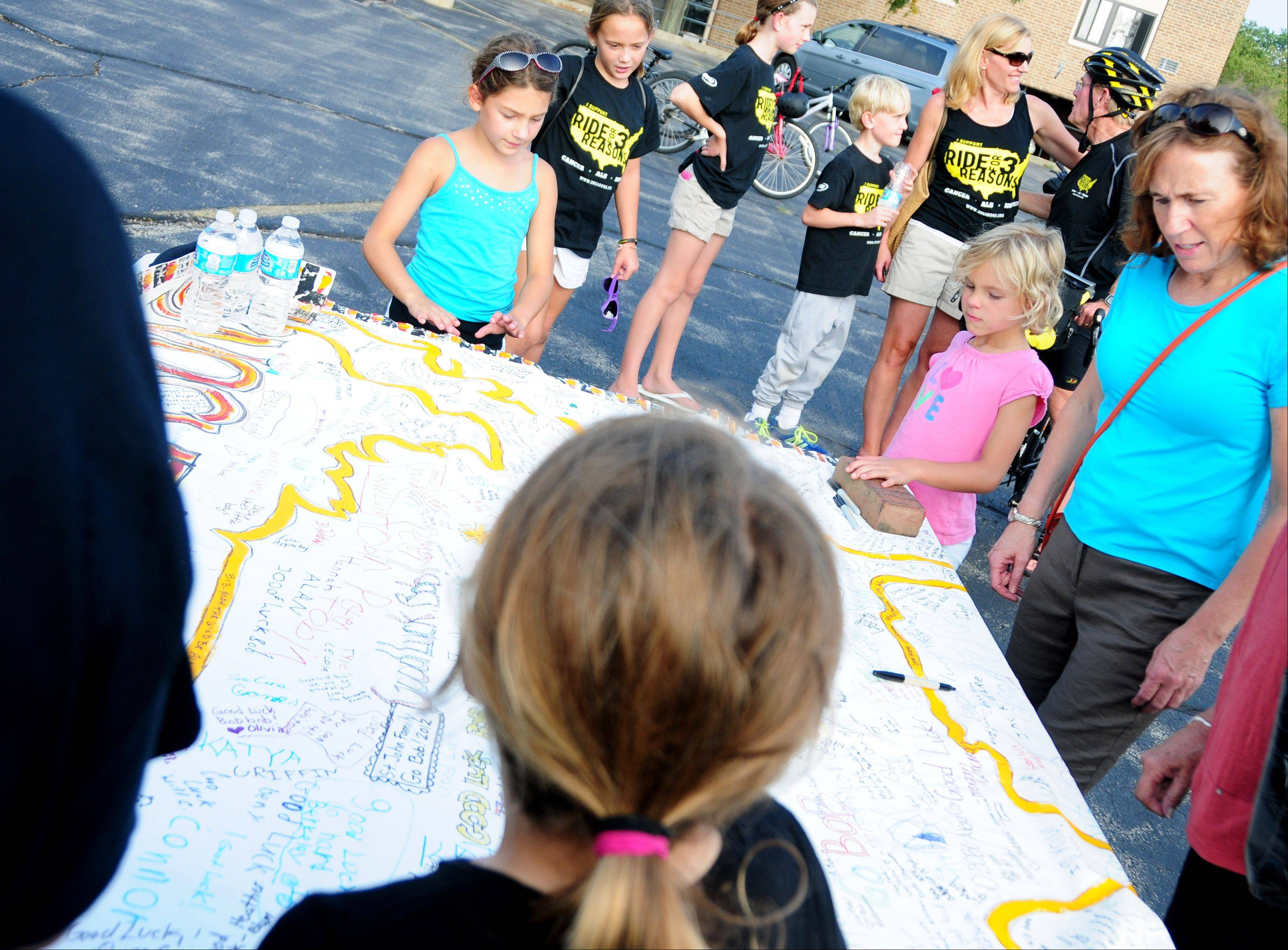 Visitors sign their names on a large map of the Ride for 3 Reasons route at a send-off party Sunday for Barrington resident Bob Lee, 70. Lee is riding his bike around the perimeter of the United States to raise money for cancer research, ALS (Lou Gehrig's disease), and hospice education.