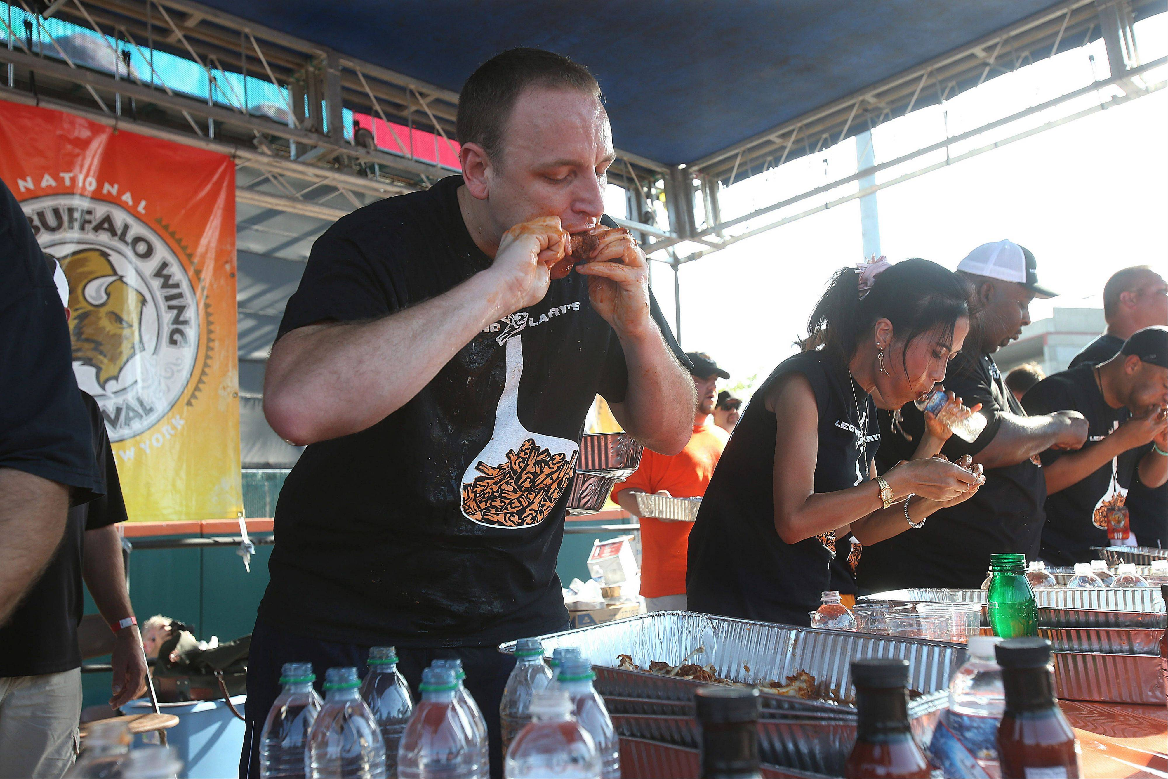 Competitive eater Joey Chestnut devours a chicken wing, on his way to eating a record 191 wings in 12 minutes, at the National Buffalo Wing Festival on Sunday in Buffalo, N.Y.