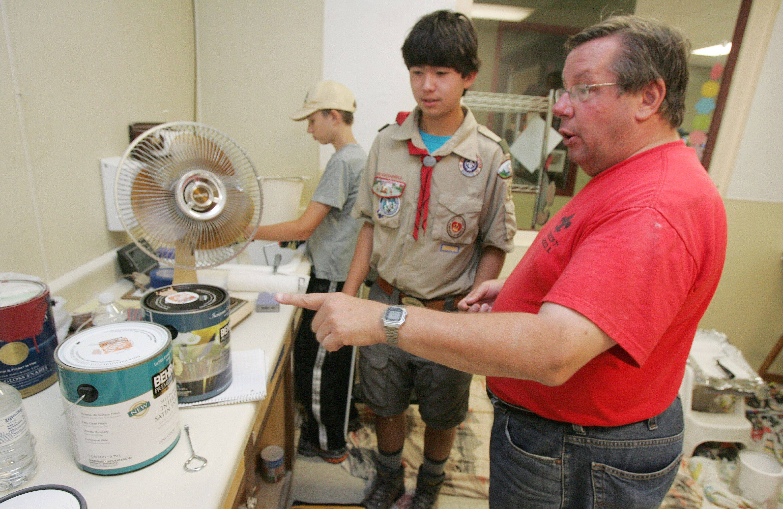 Scott Seiler of Boy Scout Troop 671, center, talks to his father, Todd, about the paint as he organizes a face lift of the Kitten Room at the Save-A-Pet Adoption Center in Grayslake Sunday. Scouts and leaders worked together on the room as part of Scott's Eagle Scout project.