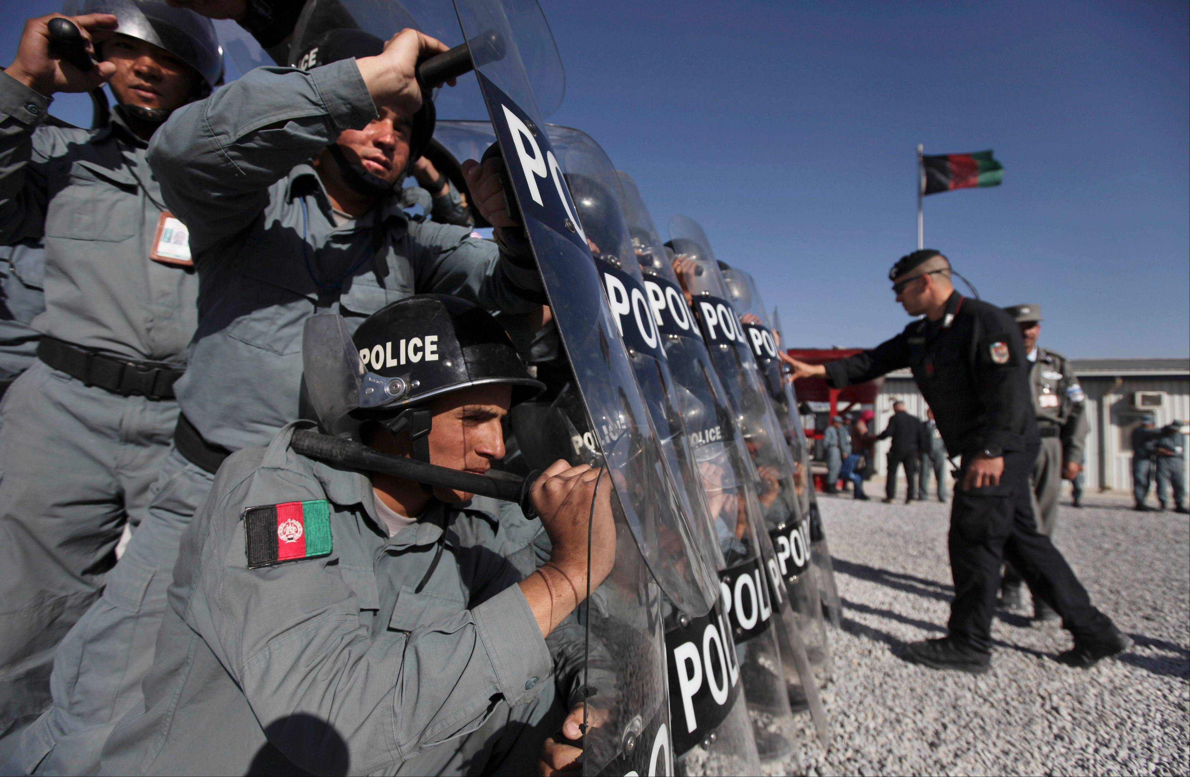 A member of Italy's carabinieri instructs new Afghan police recruits as they undergo riot control training on the outskirts of Kabul on Nov. 7, 2010. The U.S. military has suspended training for at least a month of some Afghan forces while the Americans review the process of vetting new recruits.