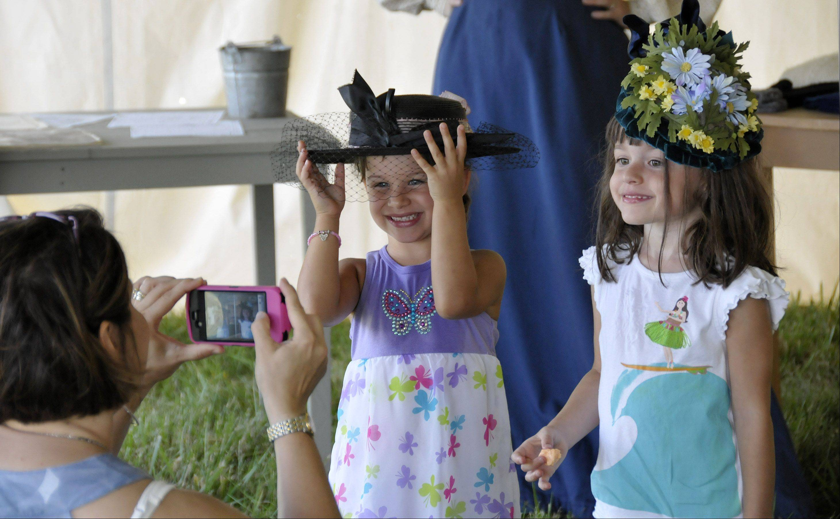 Eniko Camberis, center, and her sister, Makena, right, try on old-fashioned hats while their mother Susan Camberis, left, takes their picture Sunday during the DuPage County Forest Preserve District's old-fashioned country fair at Kline Creek Farm in West Chicago. The event gave people the experience of what an 1890s fair would have been like.