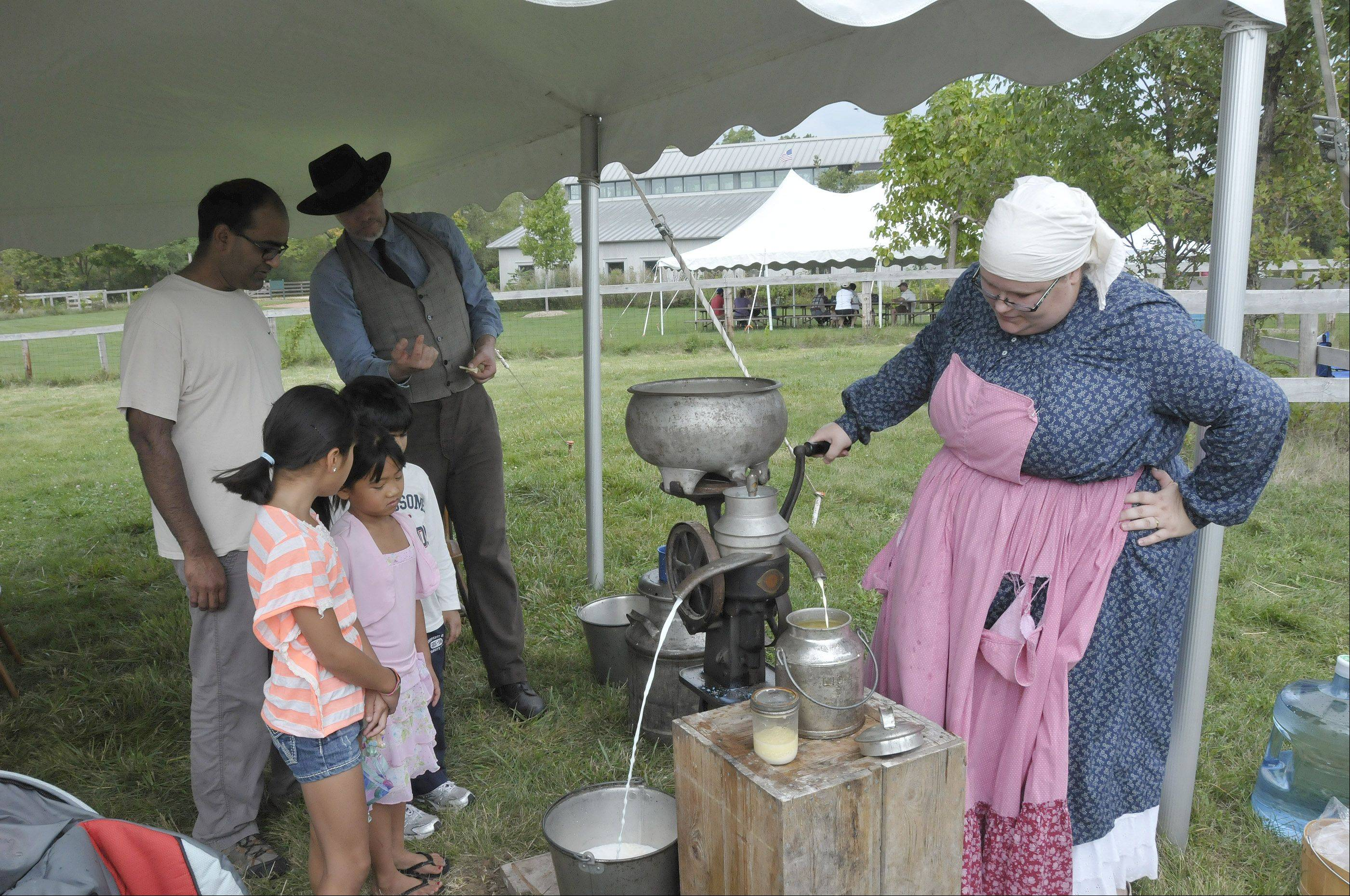 Kelly Lenza, of St. Charles, demonstrates butter making the way it was done in the 1890s during the old-fashioned country fair Sunday at Kline Creek Farm in West Chicago.