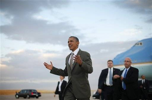 President Barack Obama, center, walking across the tarmac to greet guest upon his arrival on Air Force One, Saturday, Sept. 1, 2012, at Buckley Air Force Base in Aurora, Colo.