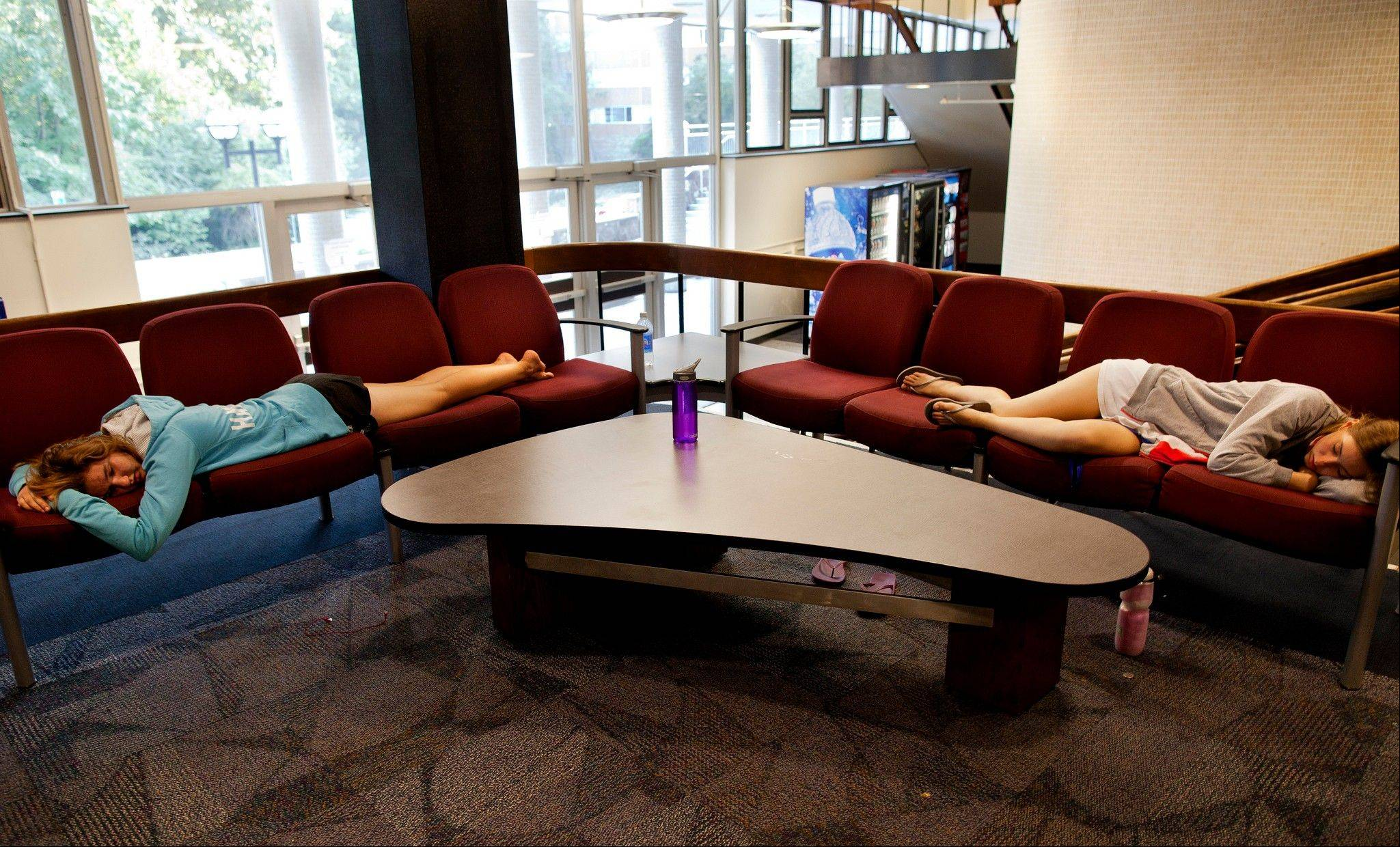 Undergraduate Engineering and Michigan Science, Technology, Engineering and Mathematics (M-STEM) Academy members Noelle Hansford, left, and Andrea Case take a nap in the lobby of Bursley Hall on the campus of the University of Michigan, in Ann Arbor, Mich. As college students return to campus in the coming weeks, they'll be showered in the usual handouts of coupons, condoms, and credit cards. But some schools are also giving students what a growing body of research reveals could make a huge difference in their college careers: ear plugs, sleep shades and napping lessons.