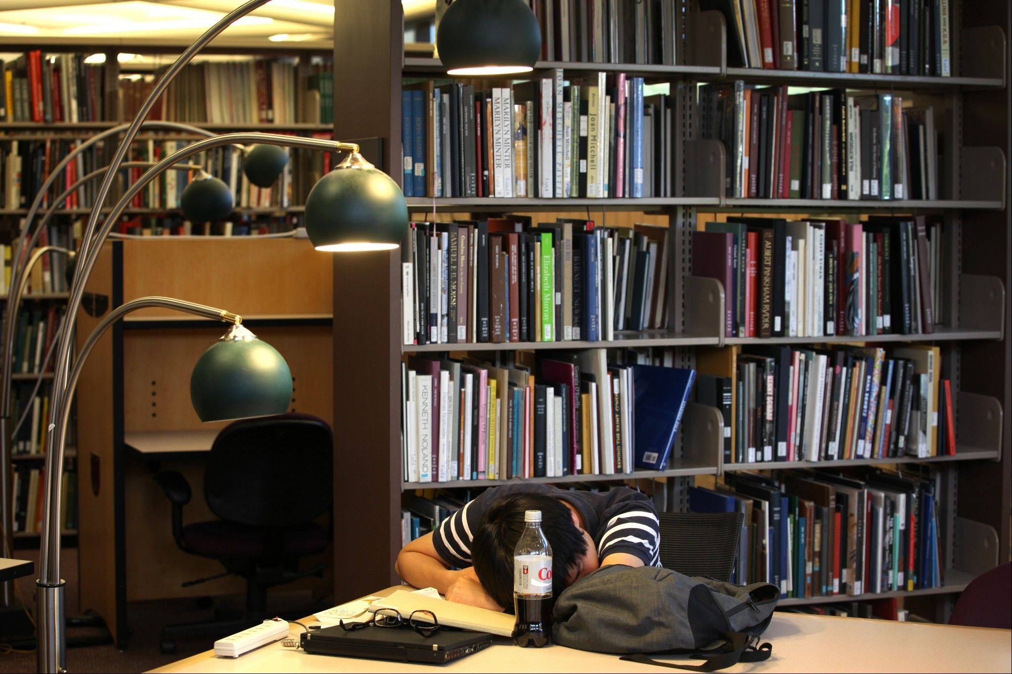 Taewon Kim, an electrical engineering systems graduate student, sleeps in the library at the Duderstandt Center on the campus of the University of Michigan, in Ann Arbor, Mich. As college students return to campus in the coming weeks, they'll be showered in the usual handouts of coupons, condoms, and credit cards. But some schools are also giving students what a growing body of research reveals could make a huge difference in their college careers: ear plugs, sleep shades and napping lessons.
