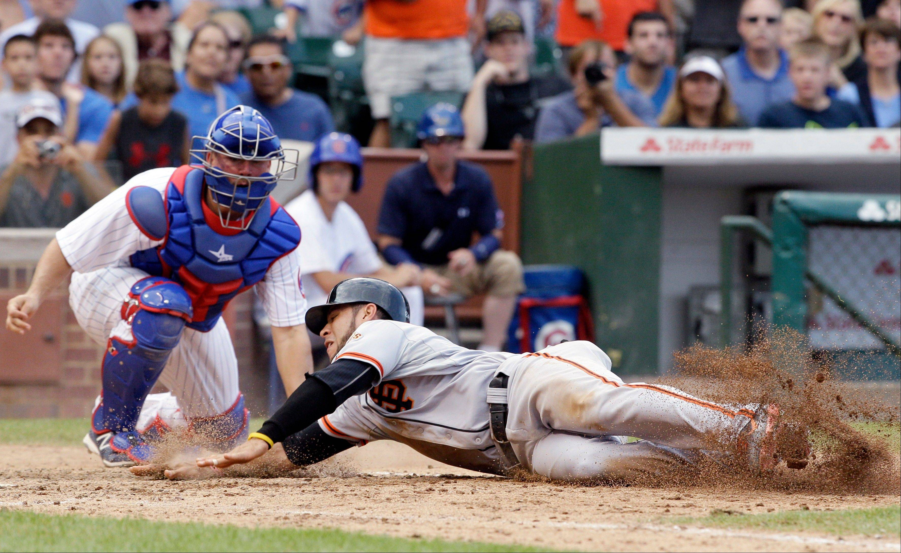 The Giants' Gregor Blanco scores what turned out to be the winning run Sunday on a single by Angel Pagan as Cubs catcher Steve Clevenger looks on in the ninth inning at Wrigley Field.