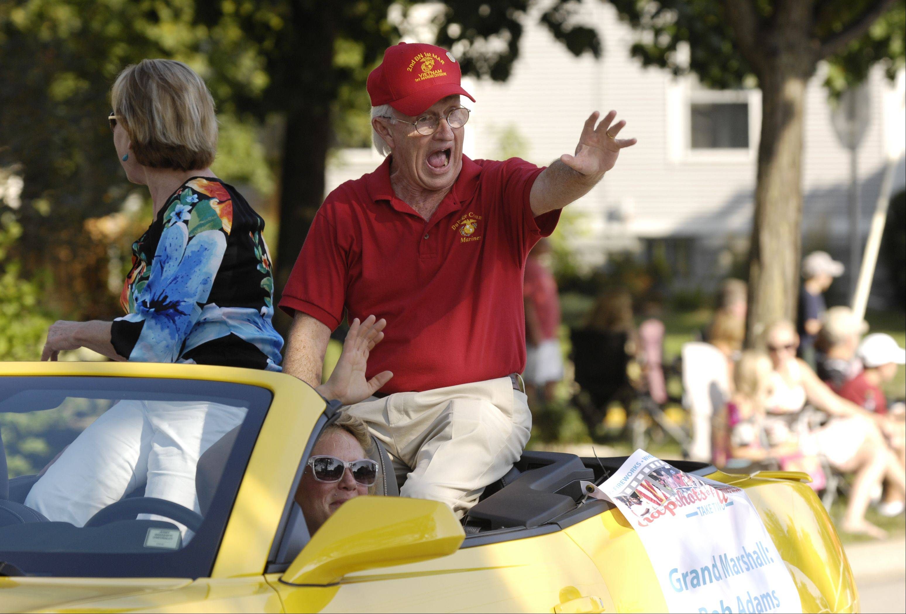 Bob Adams, founder of the Midwest Shelter for Homeless Veterans and grand marshal of the rescheduled Wheaton Fourth of July parade on Labor Day, waves to the crowds as the parade heads down Main Street. The parade was rescheduled because of storm damage from July 1.