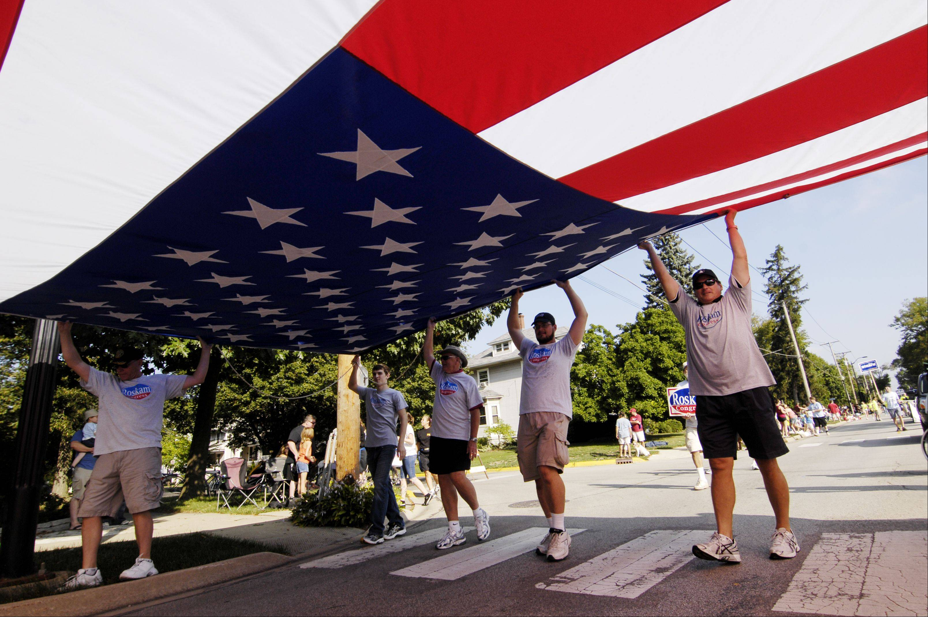 Supporters of Congressman Peter Roskam carry a huge American Flag as they march in the Wheaton Labor Day Parade Monday.