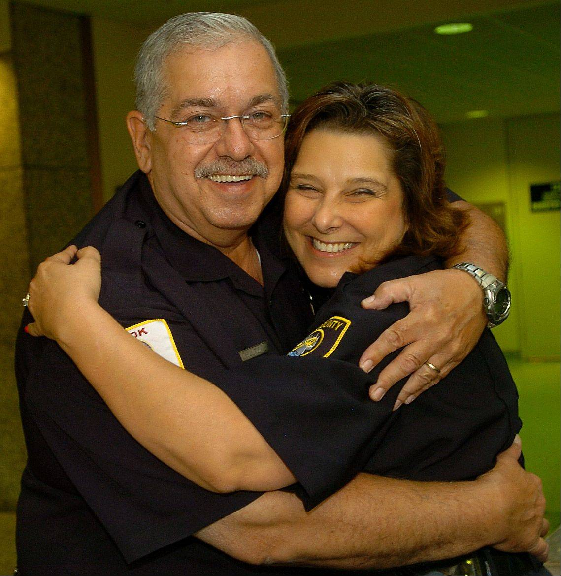 Cook County Sheriff's Deputy Stan Schultz, retiring after 46 years in law enforcement, gets a hug from Deputy Linda Bartolomeo, on his final day of work at the courthouse.