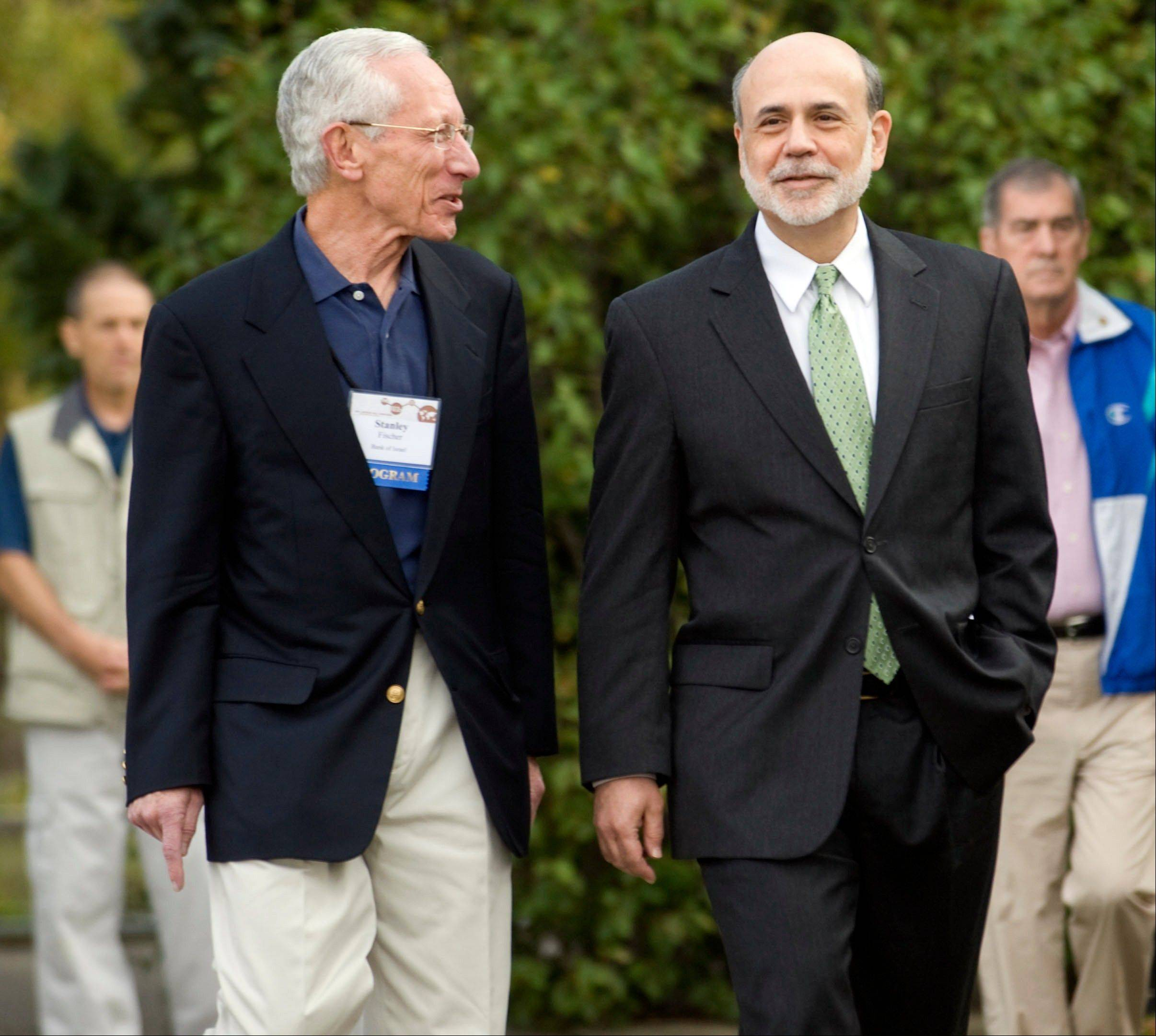 Ben S. Bernanke, chairman of the U.S. Federal Reserve, right, walks with Stanley Fischer, governor of the Bank of Israel, at the Jackson Hole economic symposium sponsored by the Kansas City Federal Reserve Bank at the Jackson Lake Lodge in Moran, Wyoming, U.S., on Friday, Aug. 31, 2012.