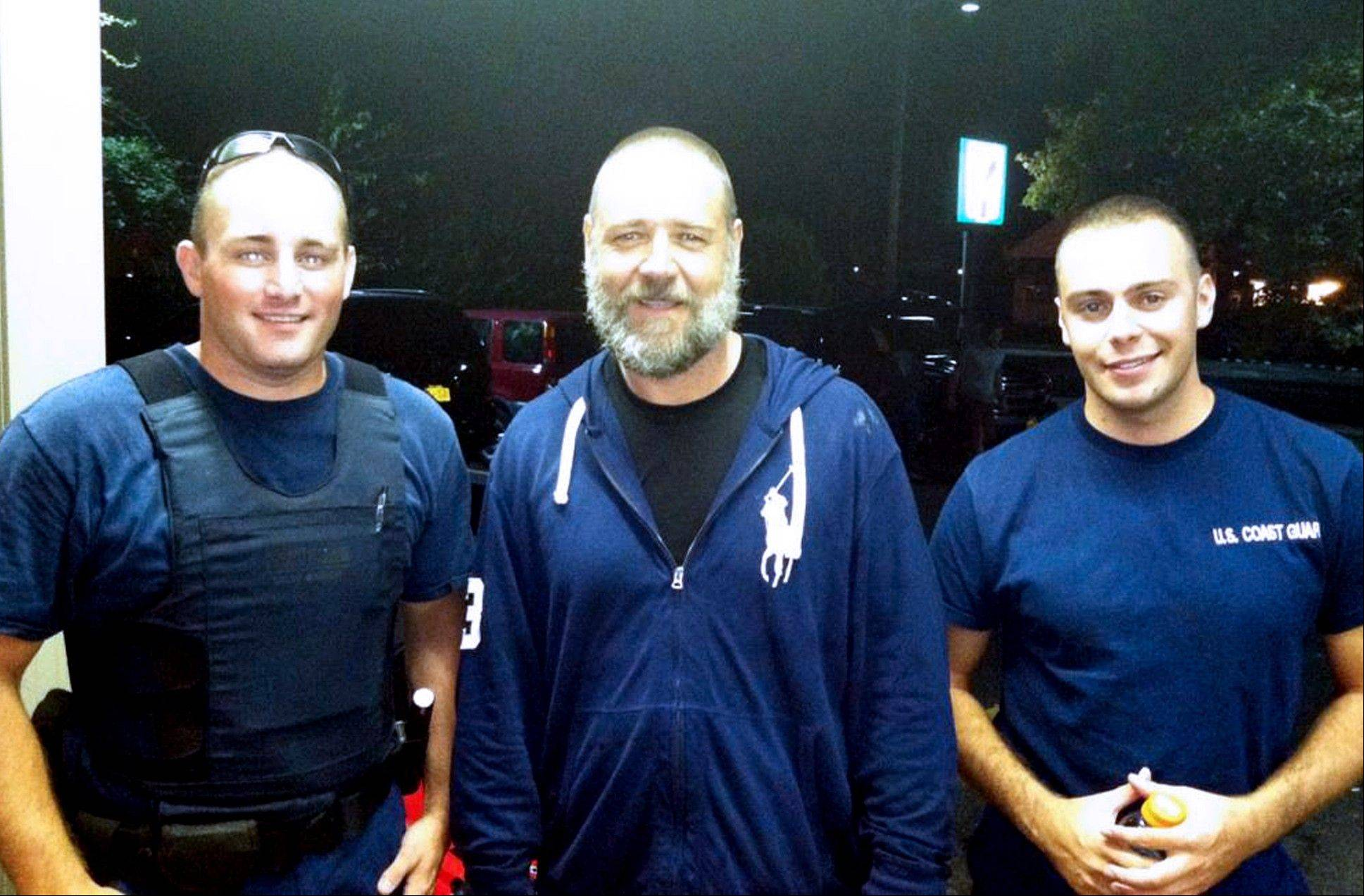 A photo provided by the U.S. Coast Guard shows Russell Crowe, center, with Coast Guard petty officers Robert Swieciki, left, and Thomas Watson Sunday Sept. 2, 2012. Crowe and a friend became disoriented while kayaking in Long Island Sound Sunday and called the Coast Guard for assistance.