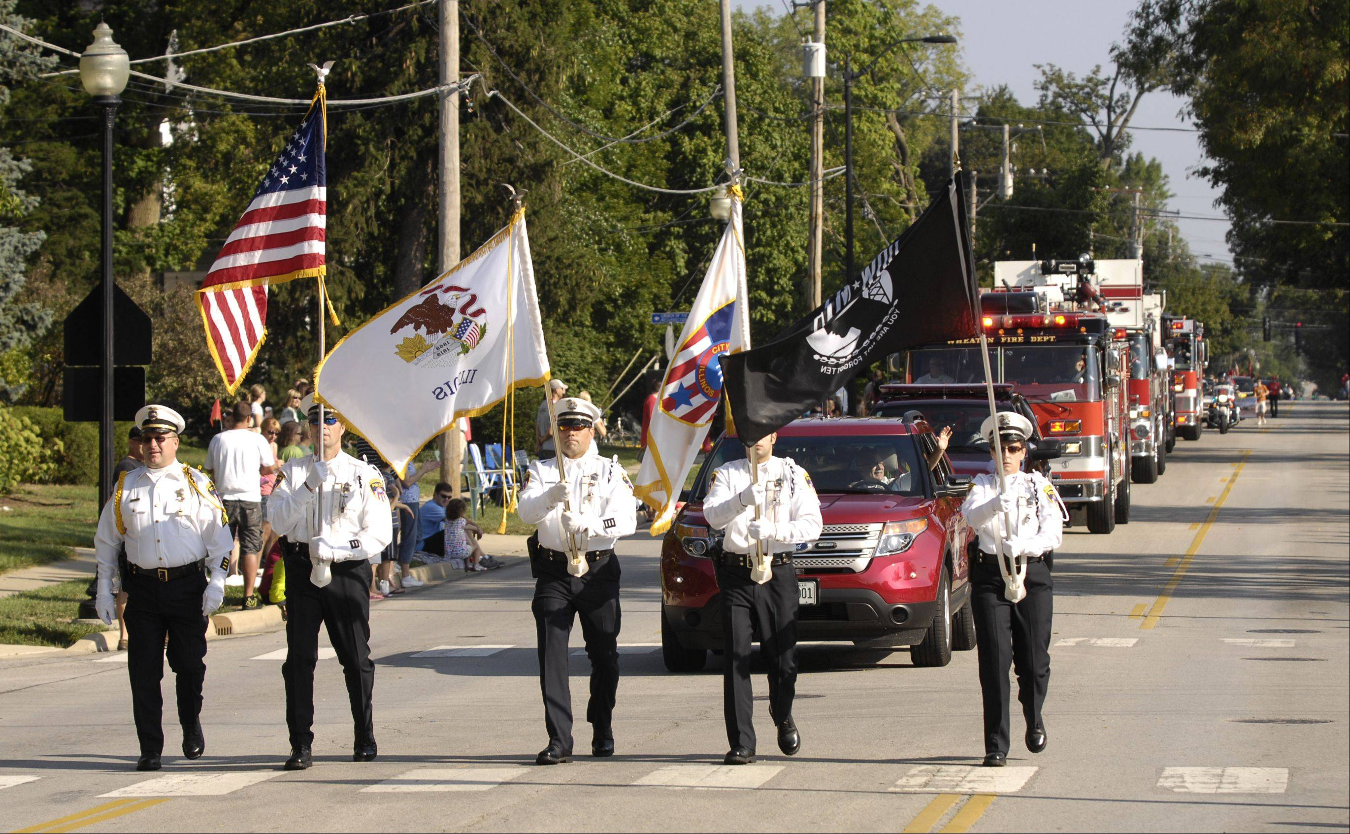 The Wheaton Police Honor Guard lead the rescheduled Wheaton Fourth of July parade on Labor Day. The parade was rescheduled because of storm damage from July 1.