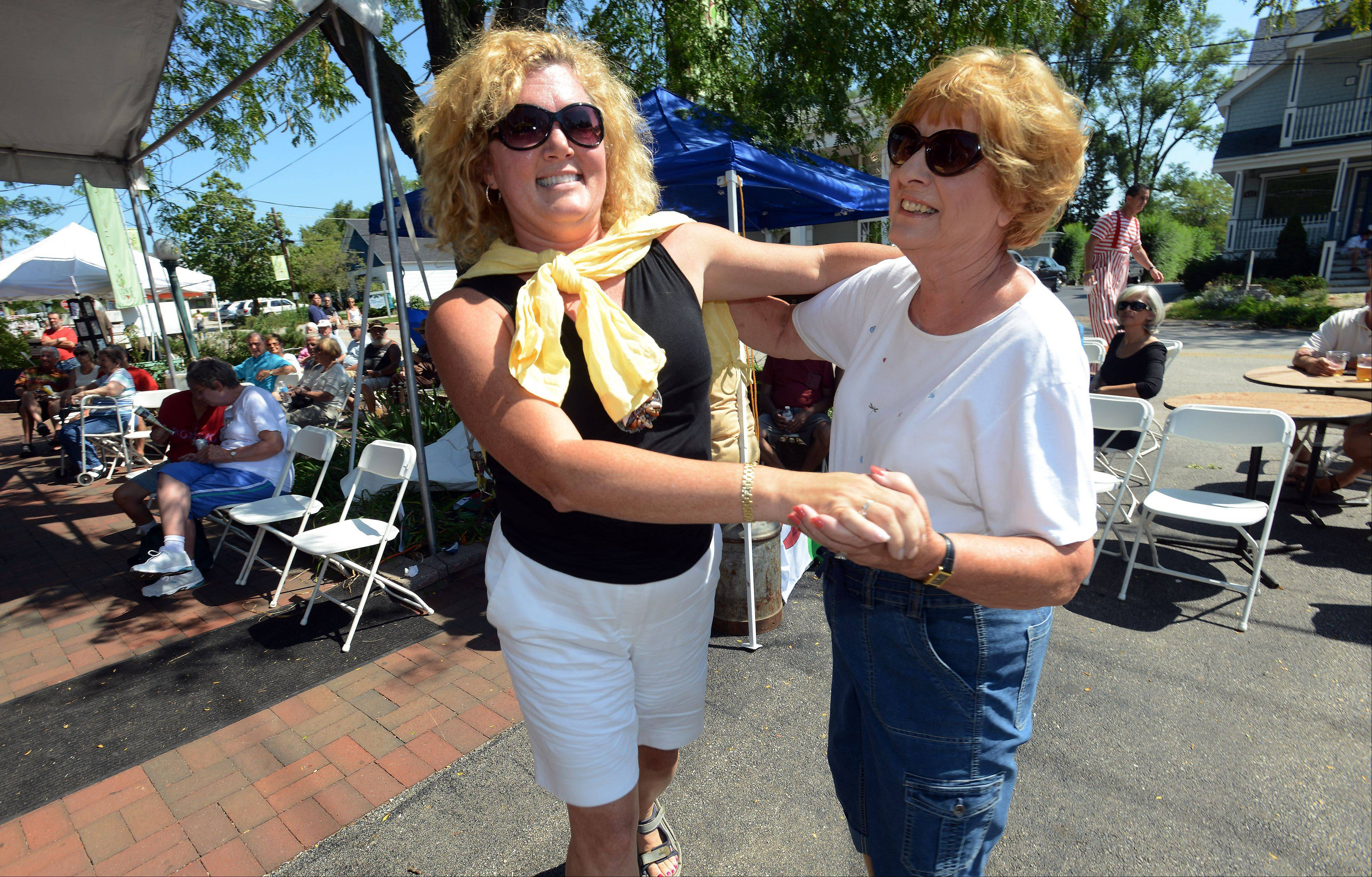 Mashelle Pavey of Naperville, left, dances with Corinne Madura of Norridge to the sounds of sweet music filling the streets of Long Grove's World Tour 2012 on Monday.