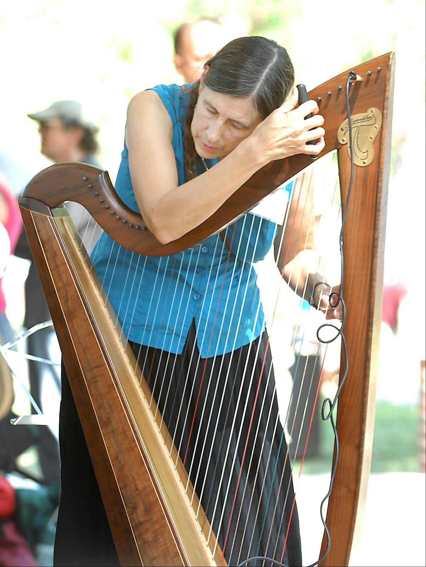 Loretta Teague of Minneapolis, Minn. tunes her harp at the 36th Annual Fox Valley Folk Music & Storytelling Festival Monday.