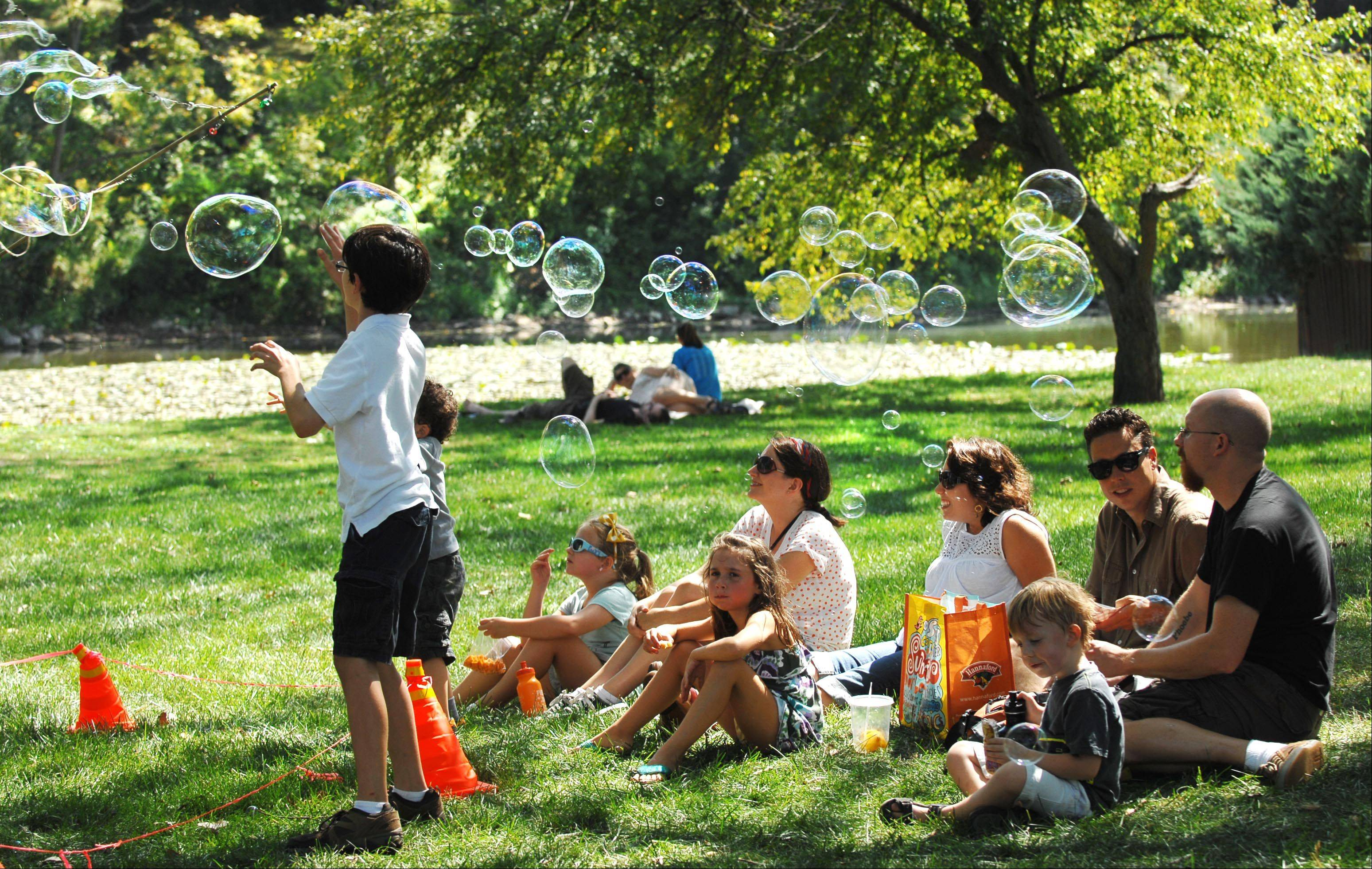 Families enjoy bubbles at the 36th Annual Fox Valley Folk Music & Storytelling Festival in Island Park in Geneva on Monday.