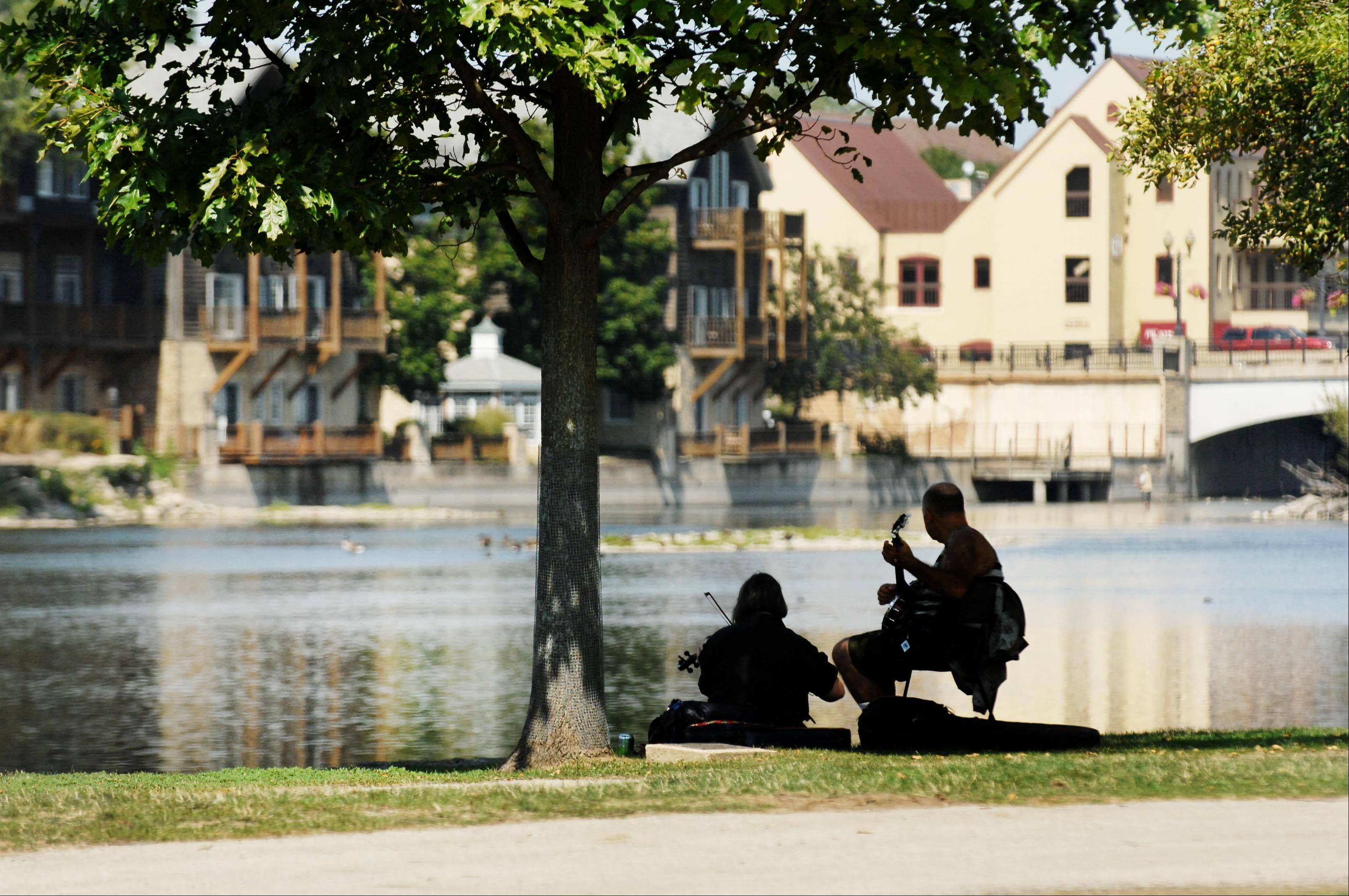 Tony Scarimbolo, of Harwood Heights, plays the banjo while Cyndy Richardson, of Wilmette, plays the fiddle in the shade by the Fox River Monday.