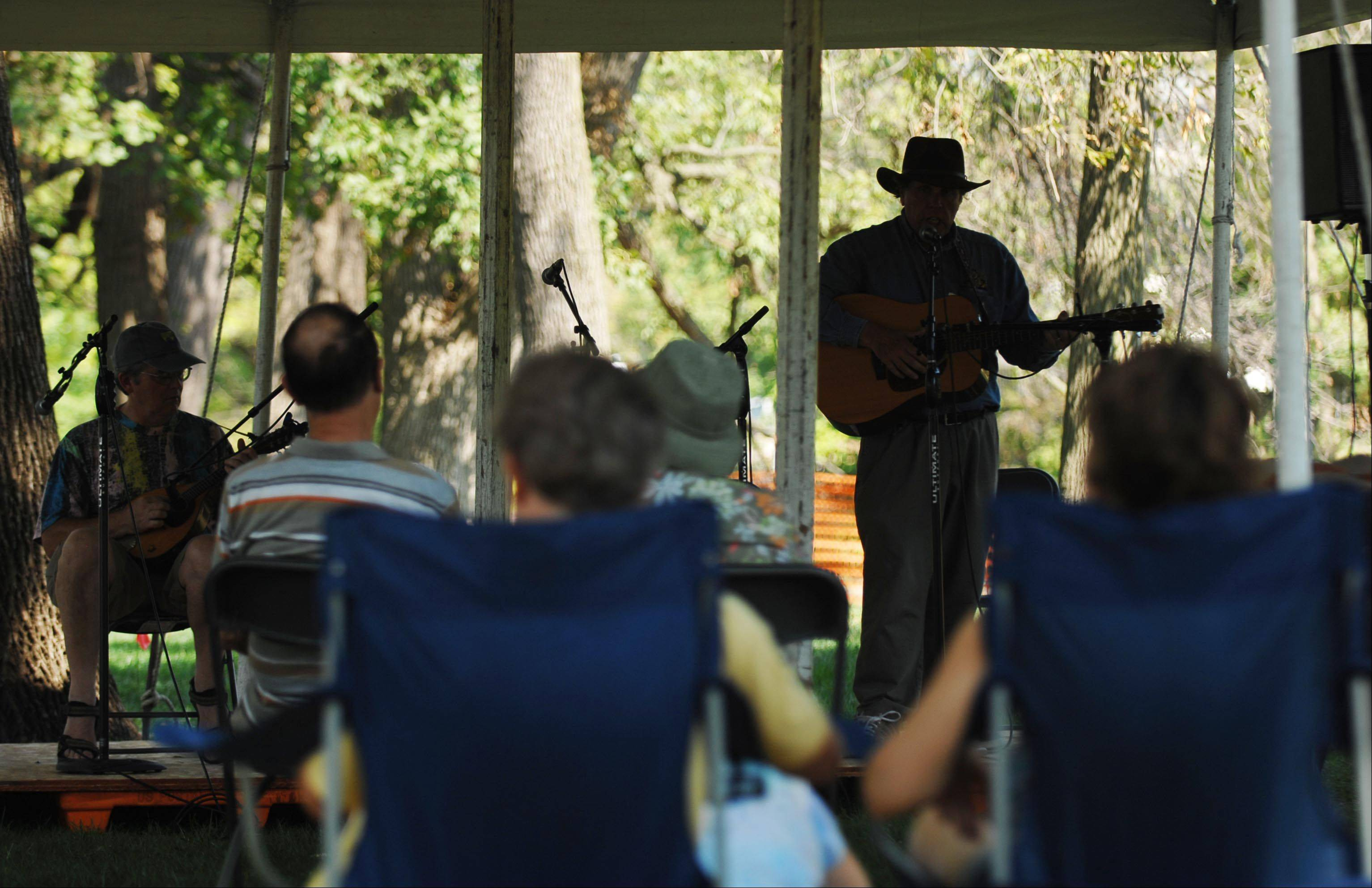 Jeff Lee of LaGrange Park plays the fiddle and Ed Ellis of Chicago plays guitar in the shade while the crowd listens at the 36th Annual Fox Valley Folk Music & Storytelling Festival in Island Park in Geneva.