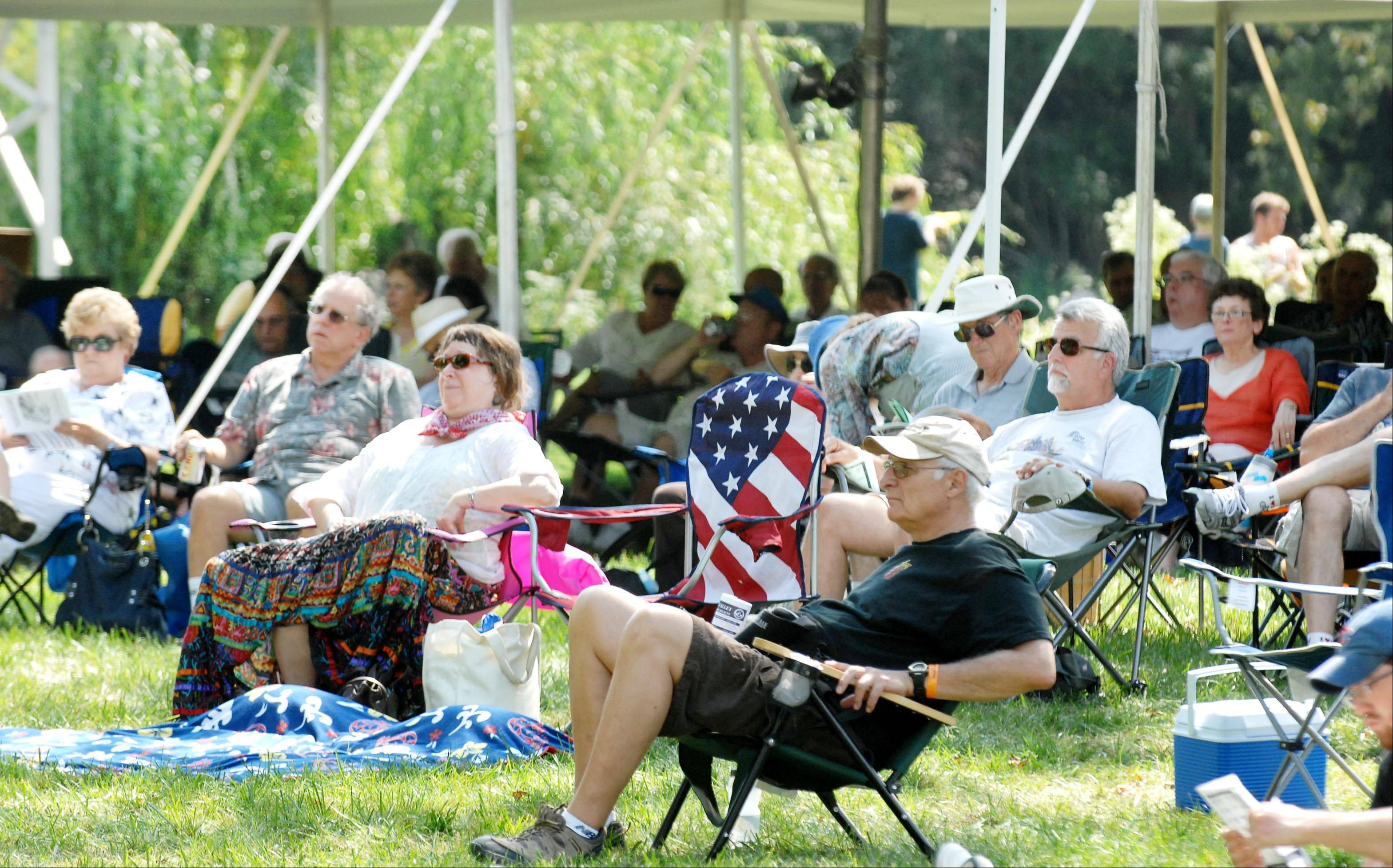 The crowd relaxes by the main stage by the Fox River at the 36th Annual Fox Valley Folk Music & Storytelling Festival in Island Park in Geneva.