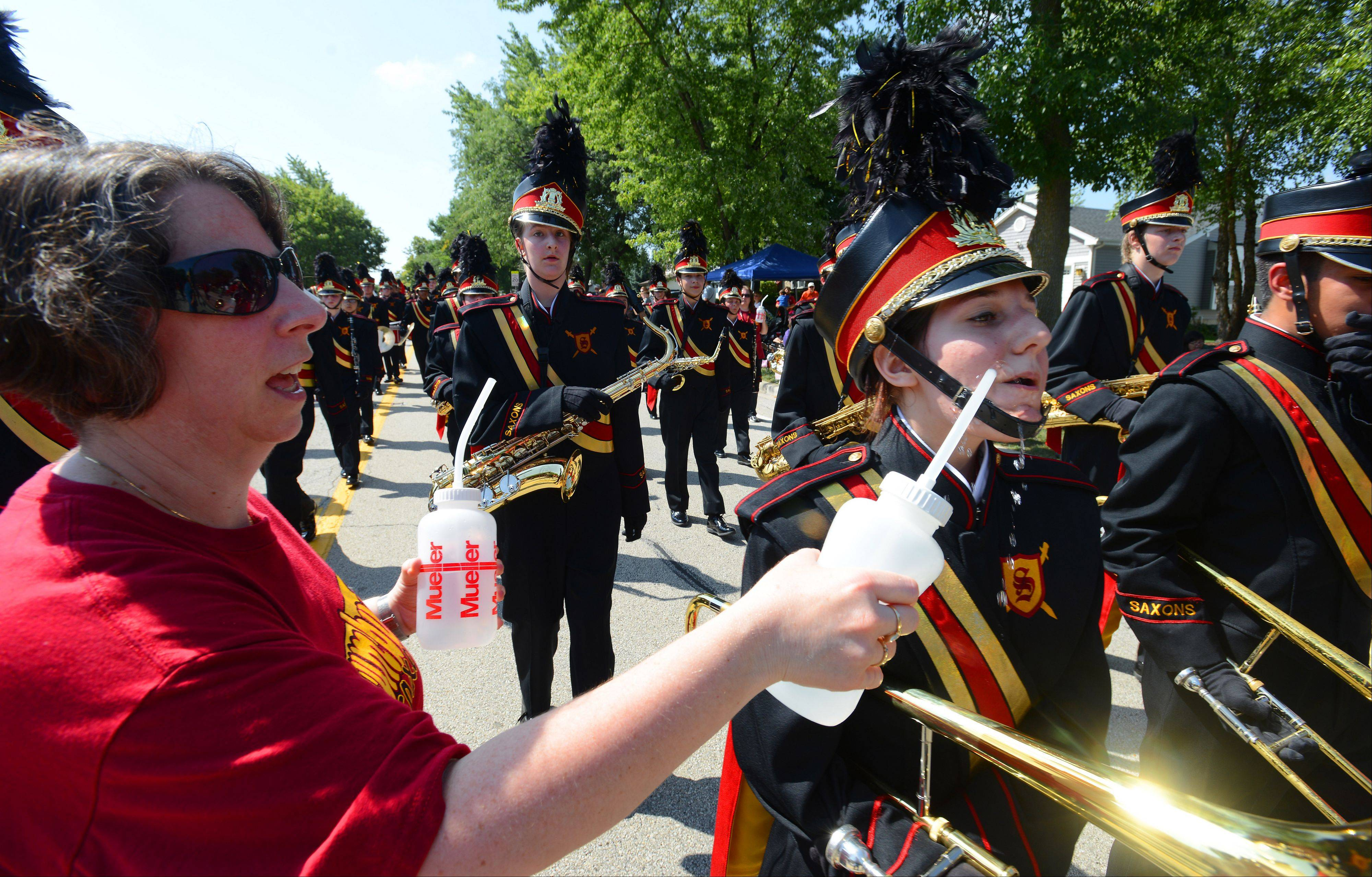 Volunteer Joelle Brescia keeps the Schaumburg High School marching band members hydrated during Monday's Labor Day parade.