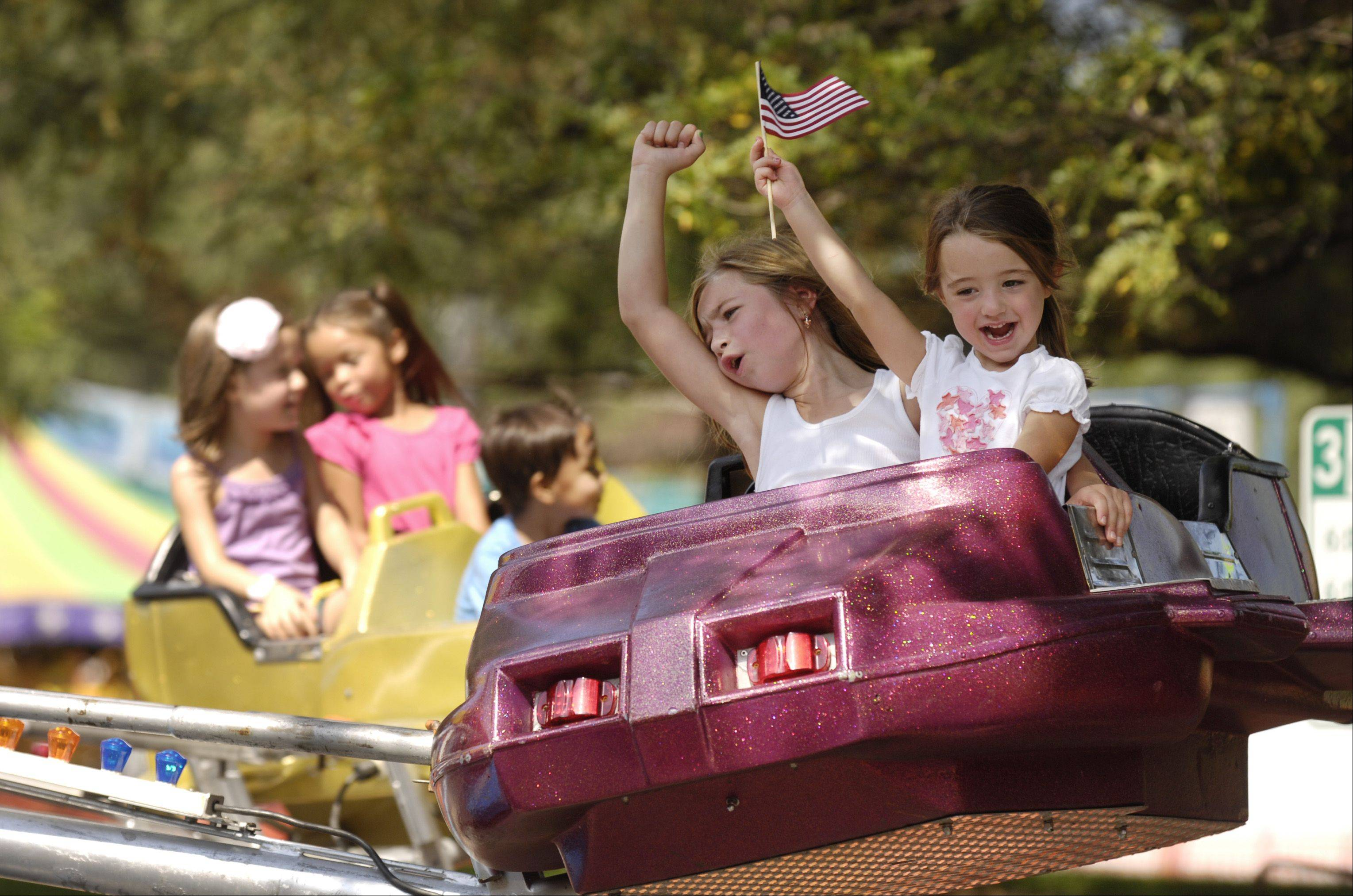 Peyton and Lexi Gilchrist of Naperville enjoy a ride at the annual Naperville Last Fling festival Monday.