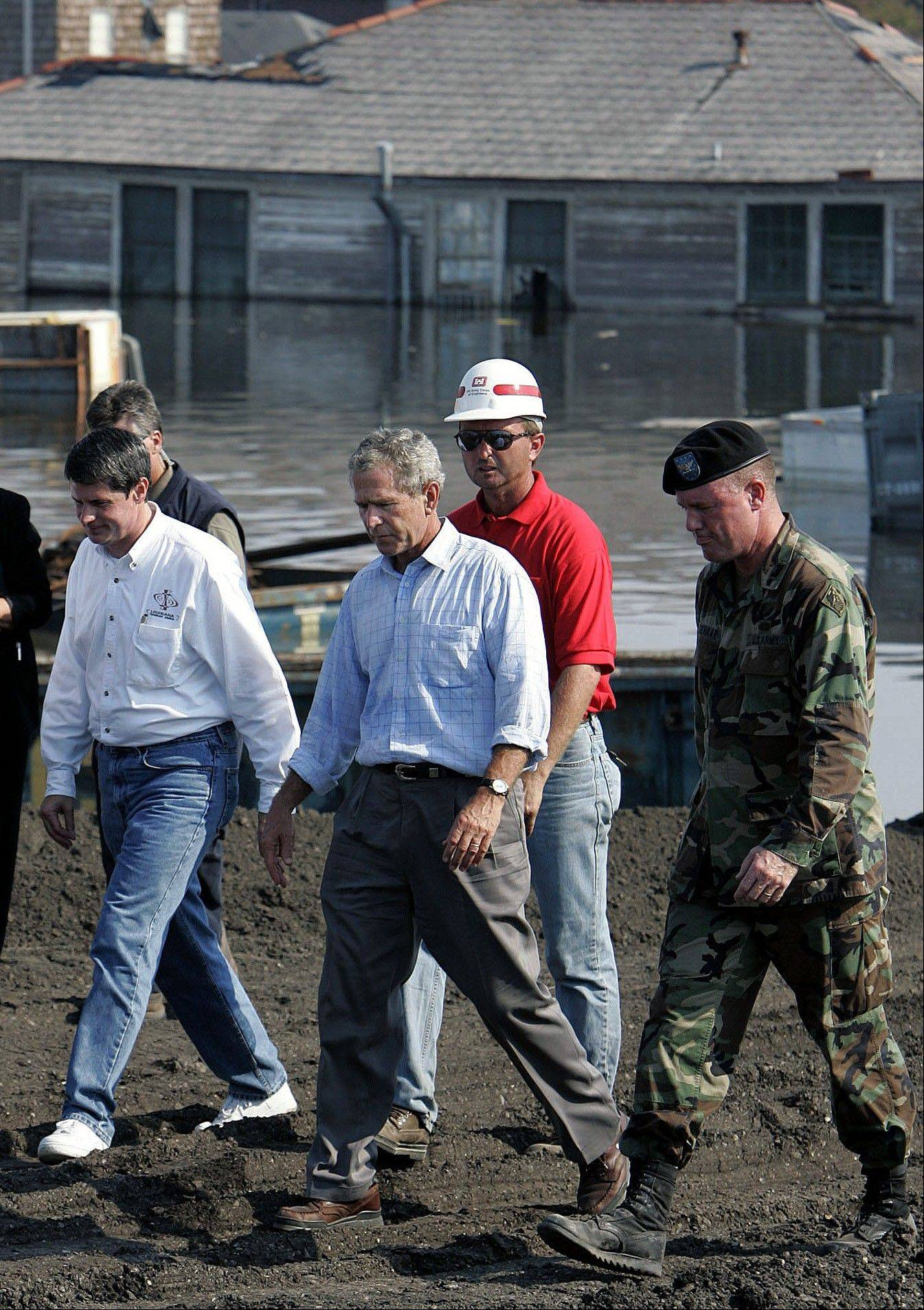 In this Sept. 2, 2005, file photo, President George Bush tours of a flooded area of New Orleans near the Seventeenth Street levee damaged by Hurricane Katrina. President Barack Obama tweaked his travel plans to head to Louisiana on Monday, Sept. 3, 2012, to see the damage from Hurricane Isaac ahead of his own nominating convention -- shortly after Republican presidential candidate Mitt Romney toured the area.