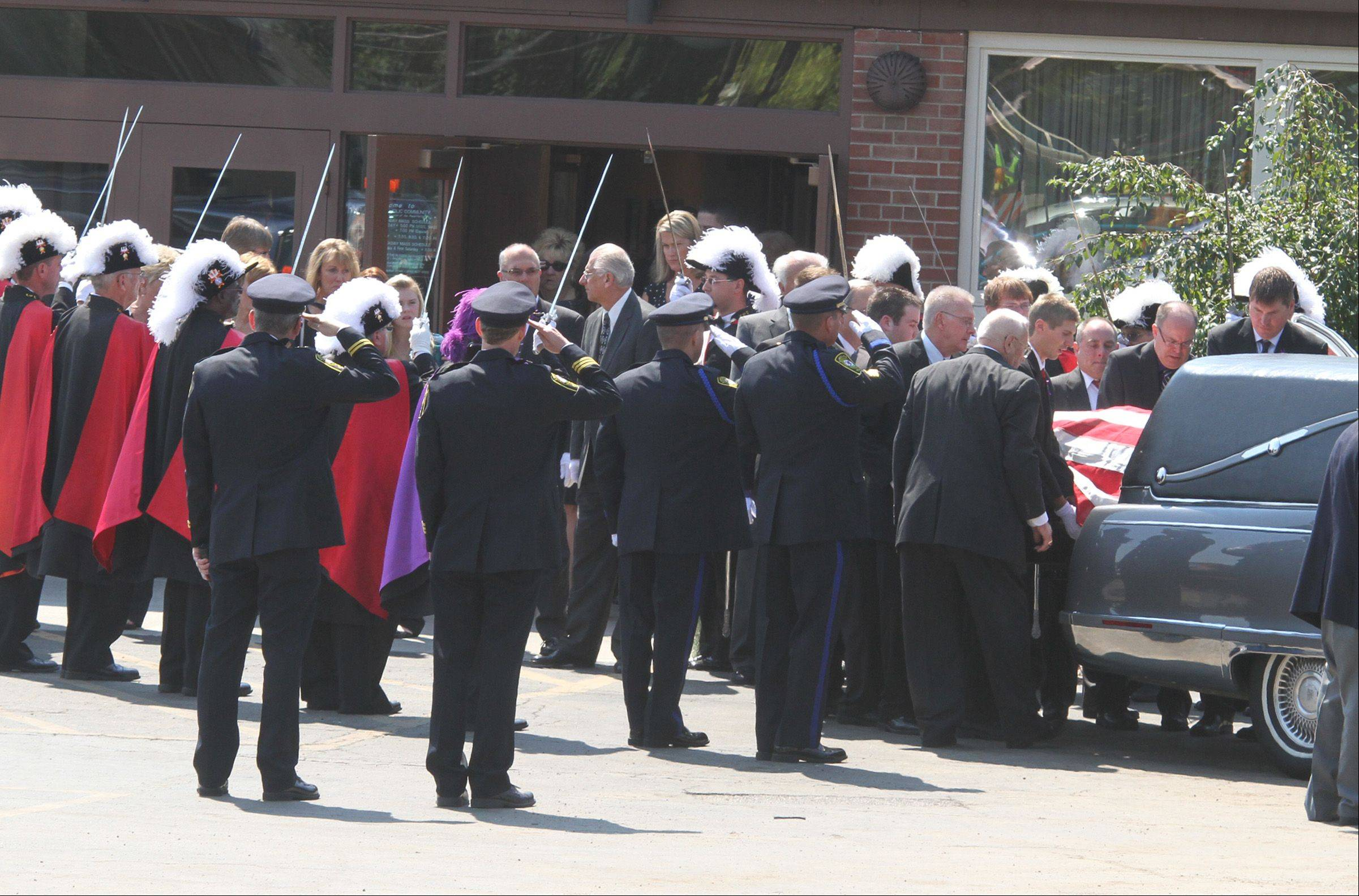 "Pallbearers carry the American flag draped casket of Lombard Village President William ""Bill"" Mueller through Knights of Columbus guards after the funeral Mass at St. Pius X Catholic Church in Lombard on Saturday, August 25."