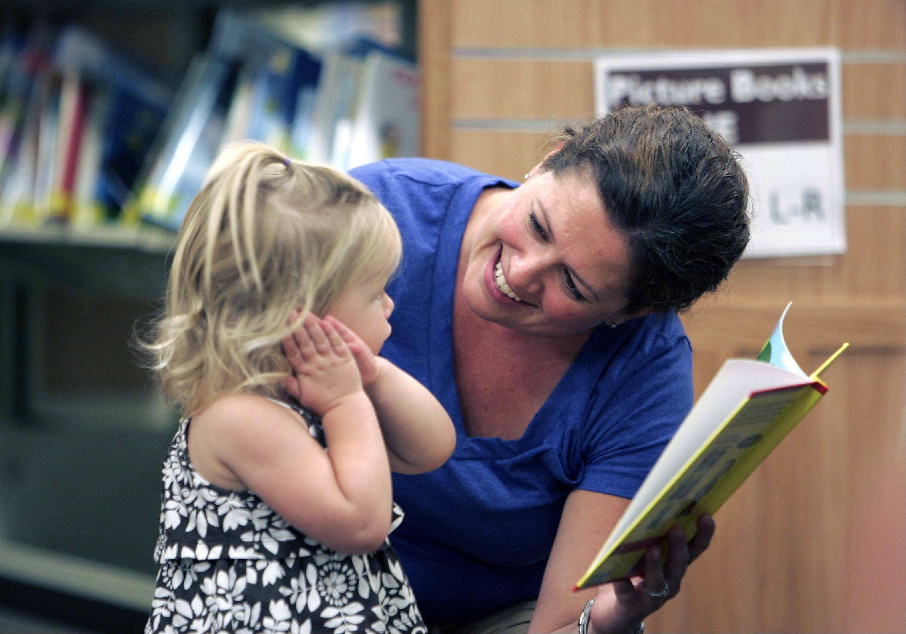 Rachel Vanderkamp of Carpentersville reads to her one-year-old daughter Nora in the West side branch of the Fox River Valley Public Library District which is in the Dundee Township Park District Randall Oaks Recreation Center in West Dundee Saturday August 25, 2012.