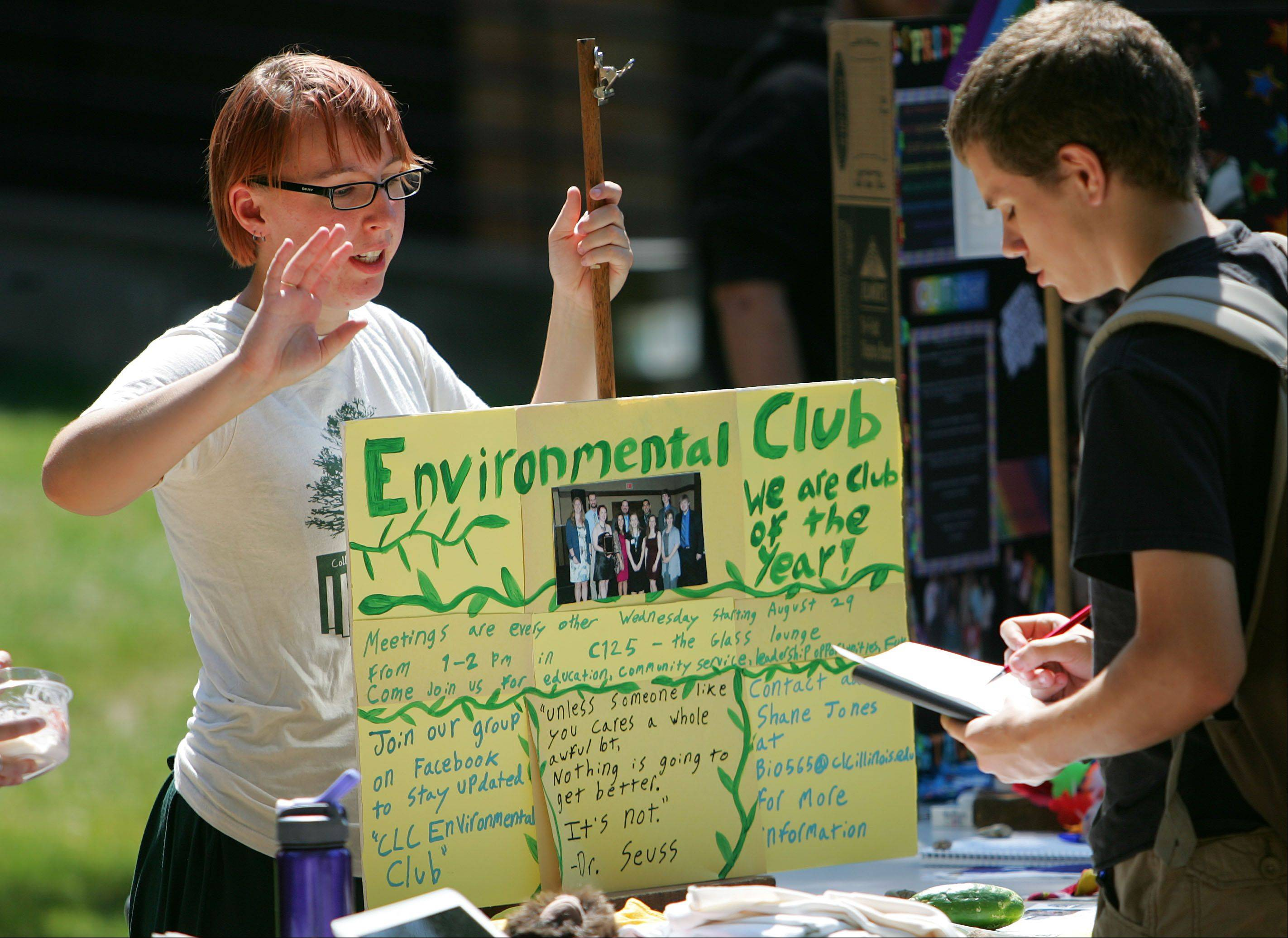 Brian Messer of Fox Lake, right, inquires about the Environmental Club to Sarah Gocek of Round Lake Park during a student activities fair at The College of Lake County Thursday.