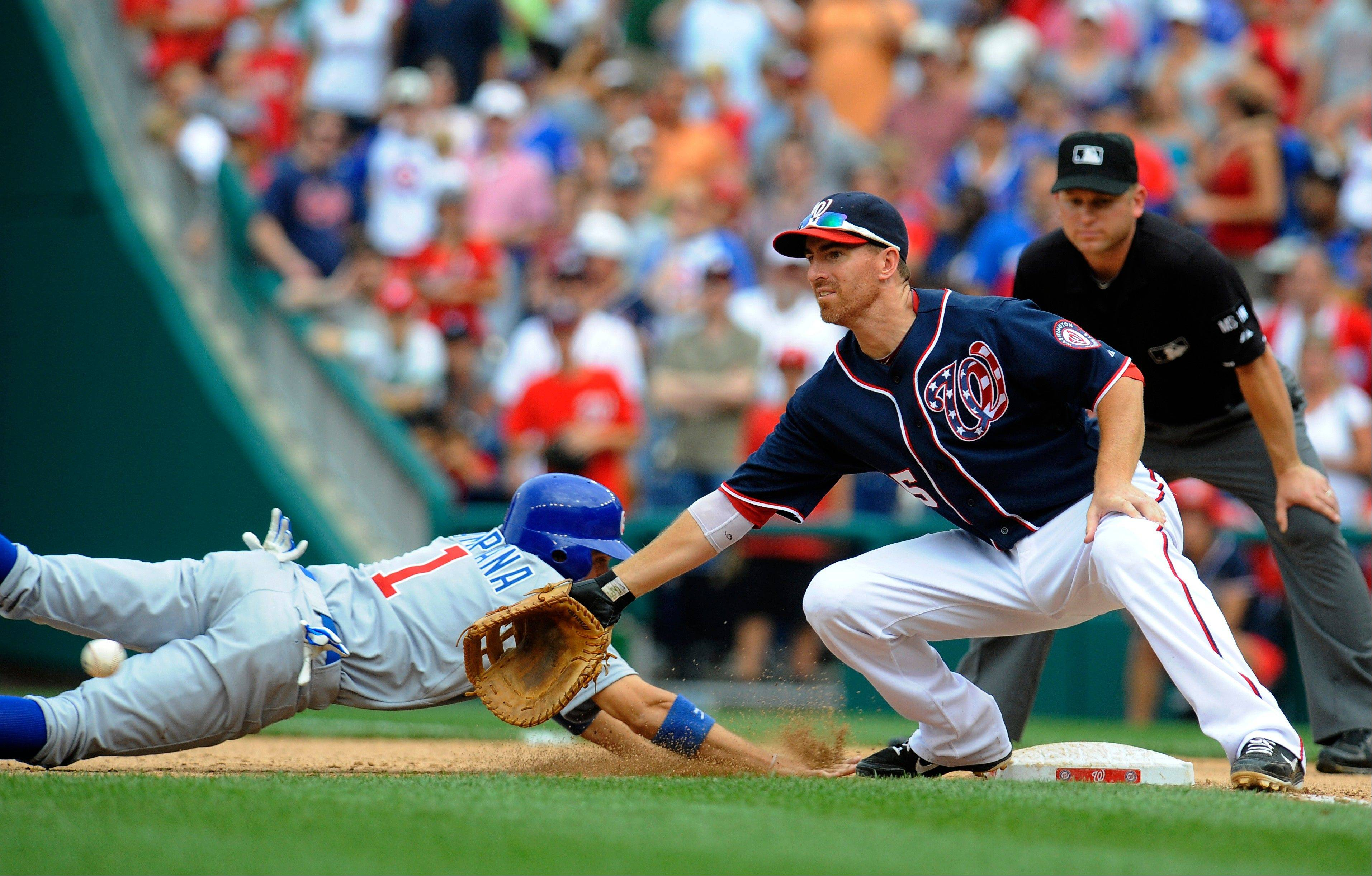 The Cubs' Tony Campana dives back to first base Monday as the Washington Nationals' Adam LaRoche tries to field a pick-off attempt by pitcher Tyler Clippard during the ninth inning at Nationals Park.