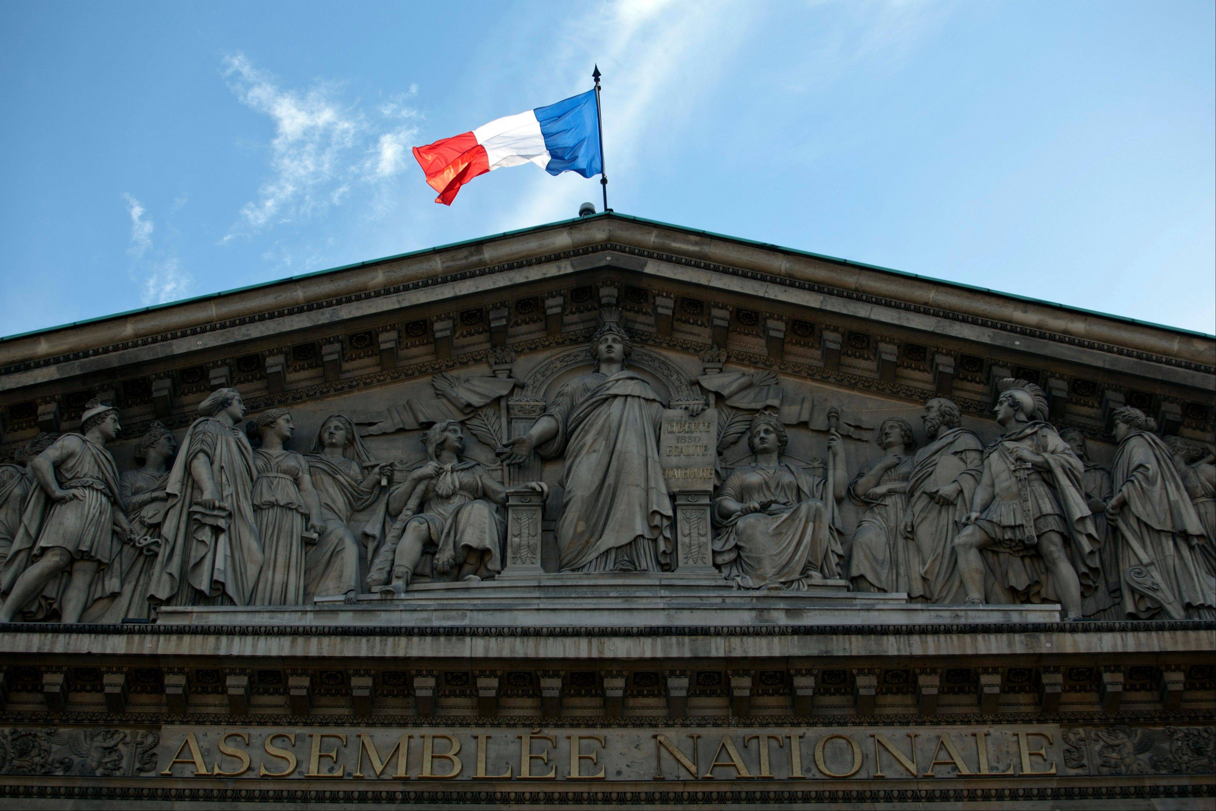 The French national flag flies atop the National Assembly building in Paris, France. Europe's economy is edging toward a recession as budget cuts from Spain to Ireland undermine consumer spending and company investment just as global demand shows signs of cooling.