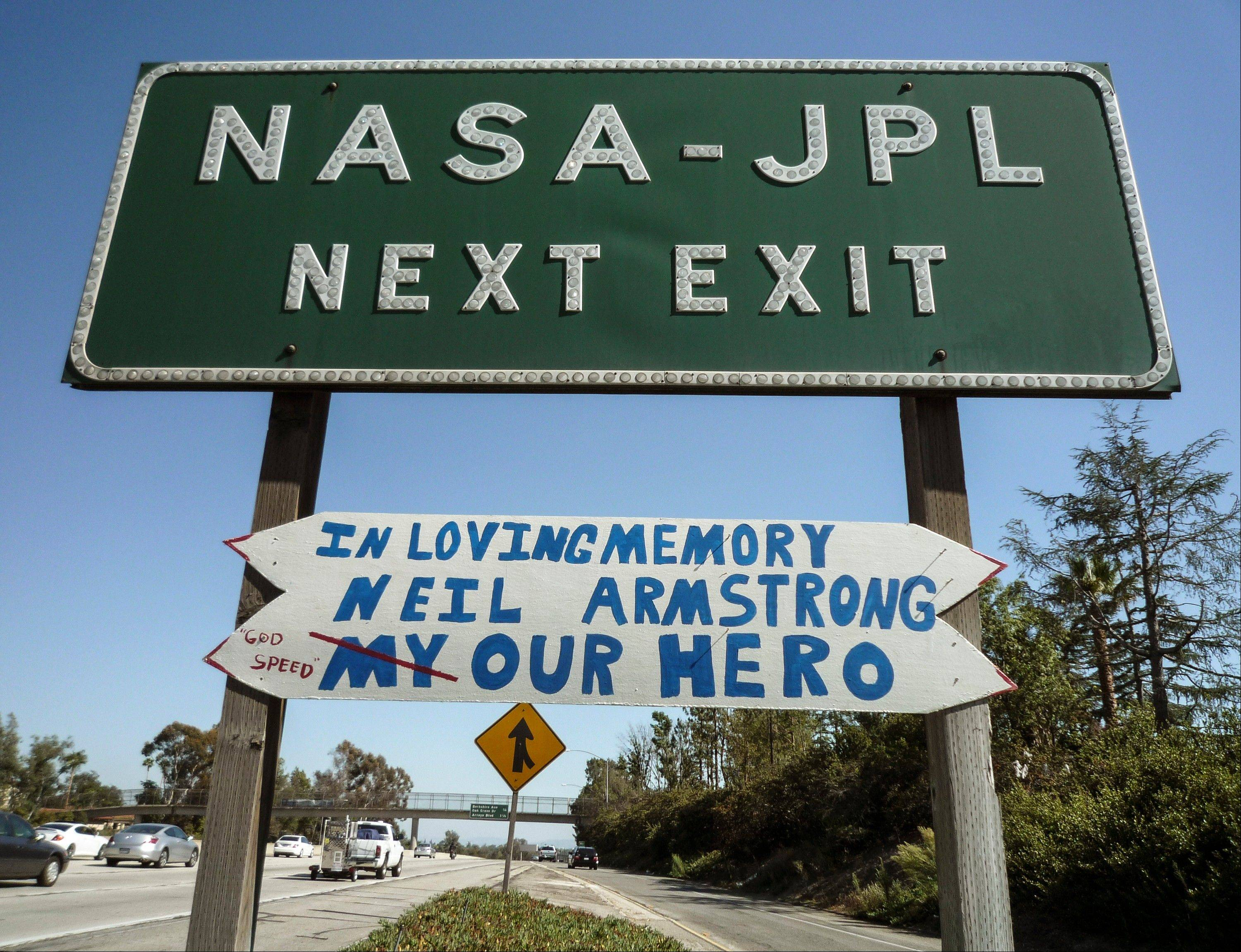 A handmade sign honoring astronaut Neil Armstrong is hung under a freeway off-ramp sign at the NASA-JPL exit on the CA-210 Freeway in Pasadena, Calif. Armstrong, the first man on the moon, inspired millions with his moonwalk.