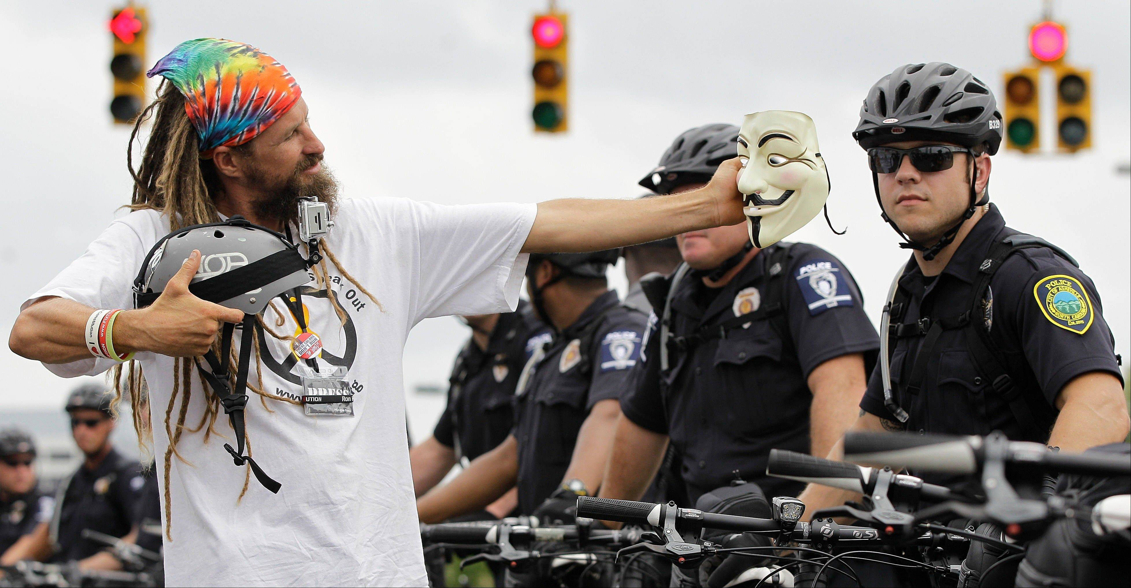 An Occupy Demonstrator takes a photo with his mask during an unscheduled protest march, Tuesday, Sept. 4, 2012, in Charlotte, N.C. The Democratic National Convention begins today.