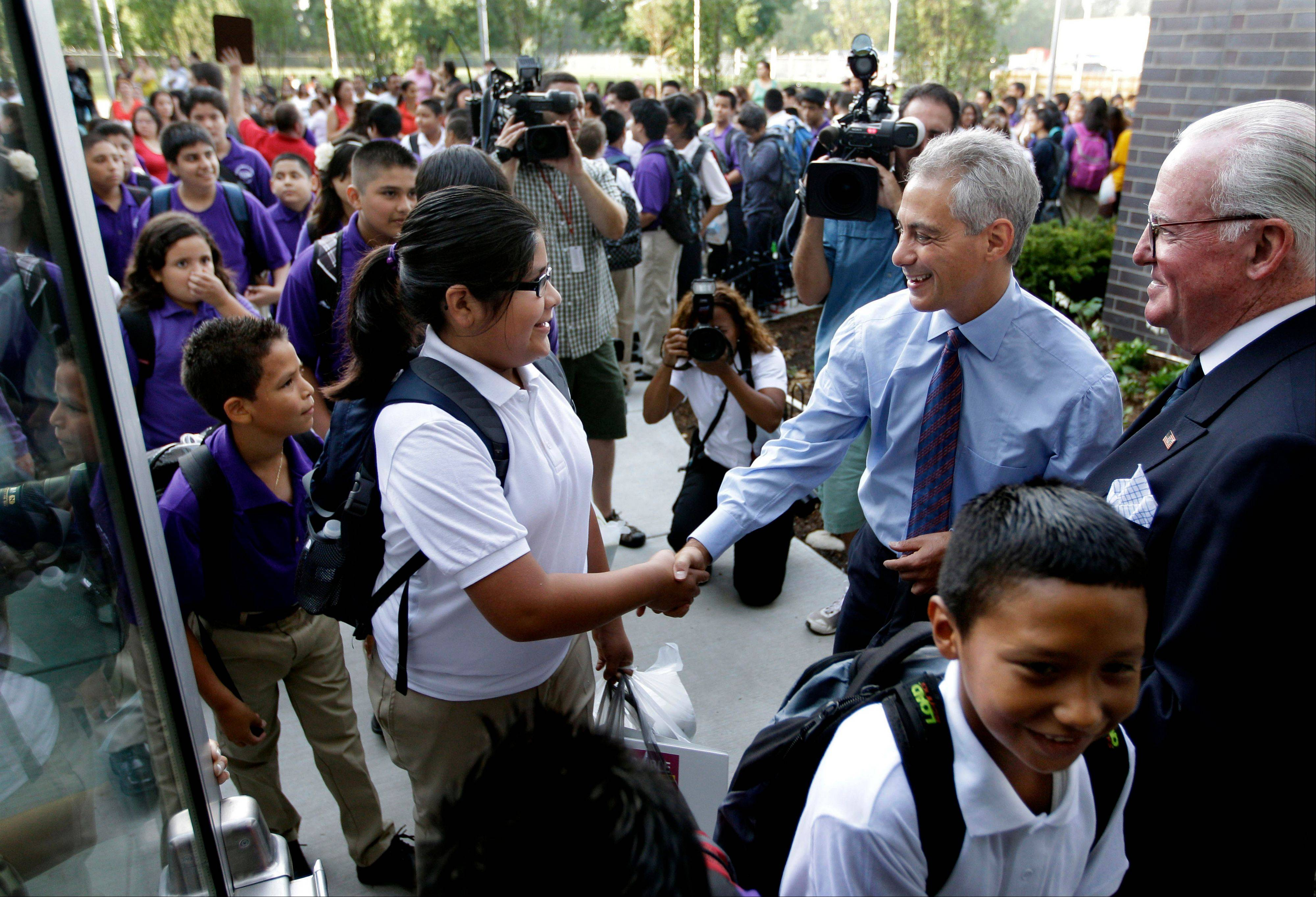 Chicago Mayor Rahm Emanuel and Alderman Ed Burke greet students Tuesday as they enter Shields Middle School on their first day back to school in Chicago.