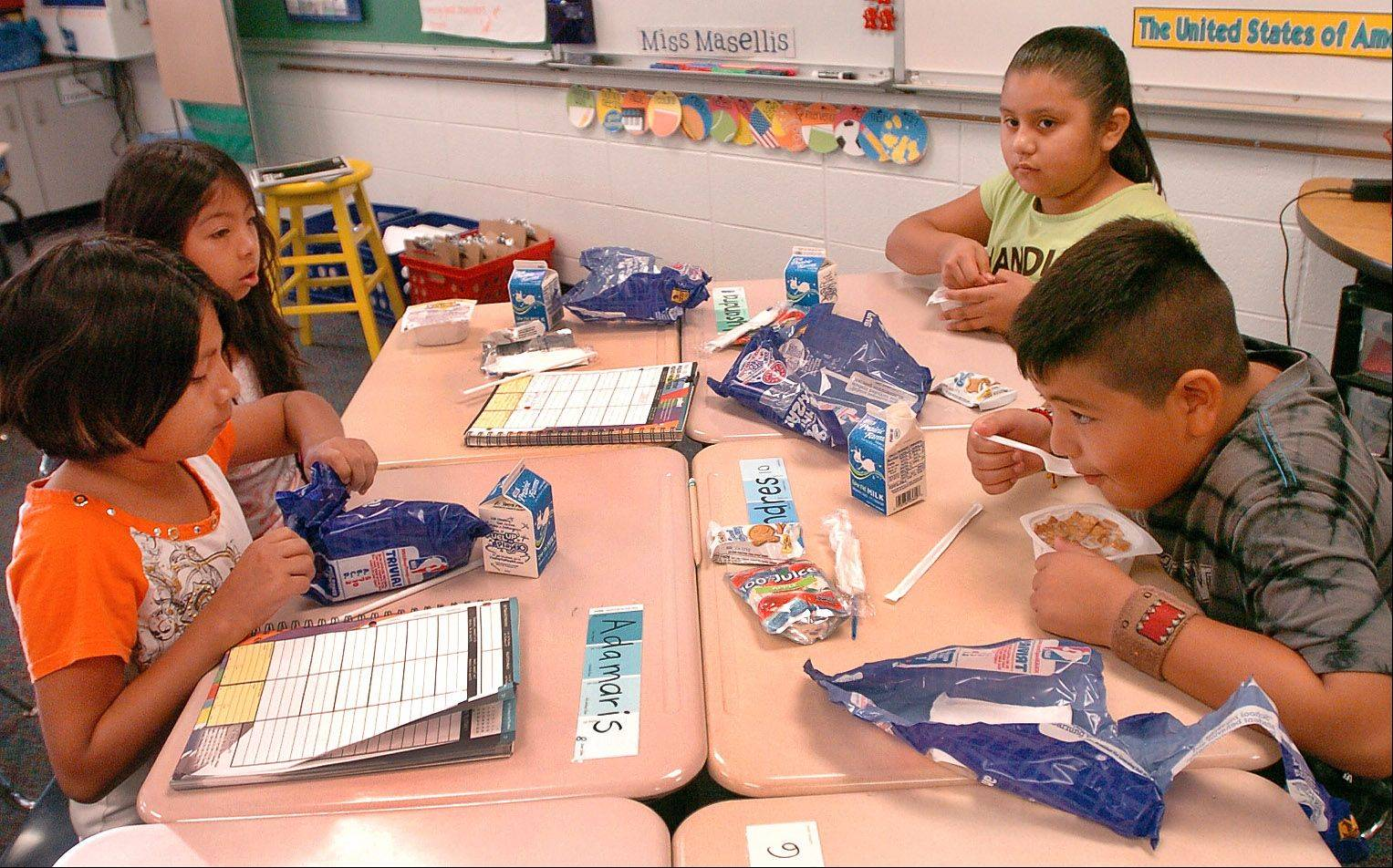 Fourth graders from left, Naomi Hildago, Italletzy Magdaleno, Lysandra Colin and Andres Garcia eat breakfast in their classroom as part of a new universally free breakfast program being piloted at Jane Addams Elementary School in Palatine.