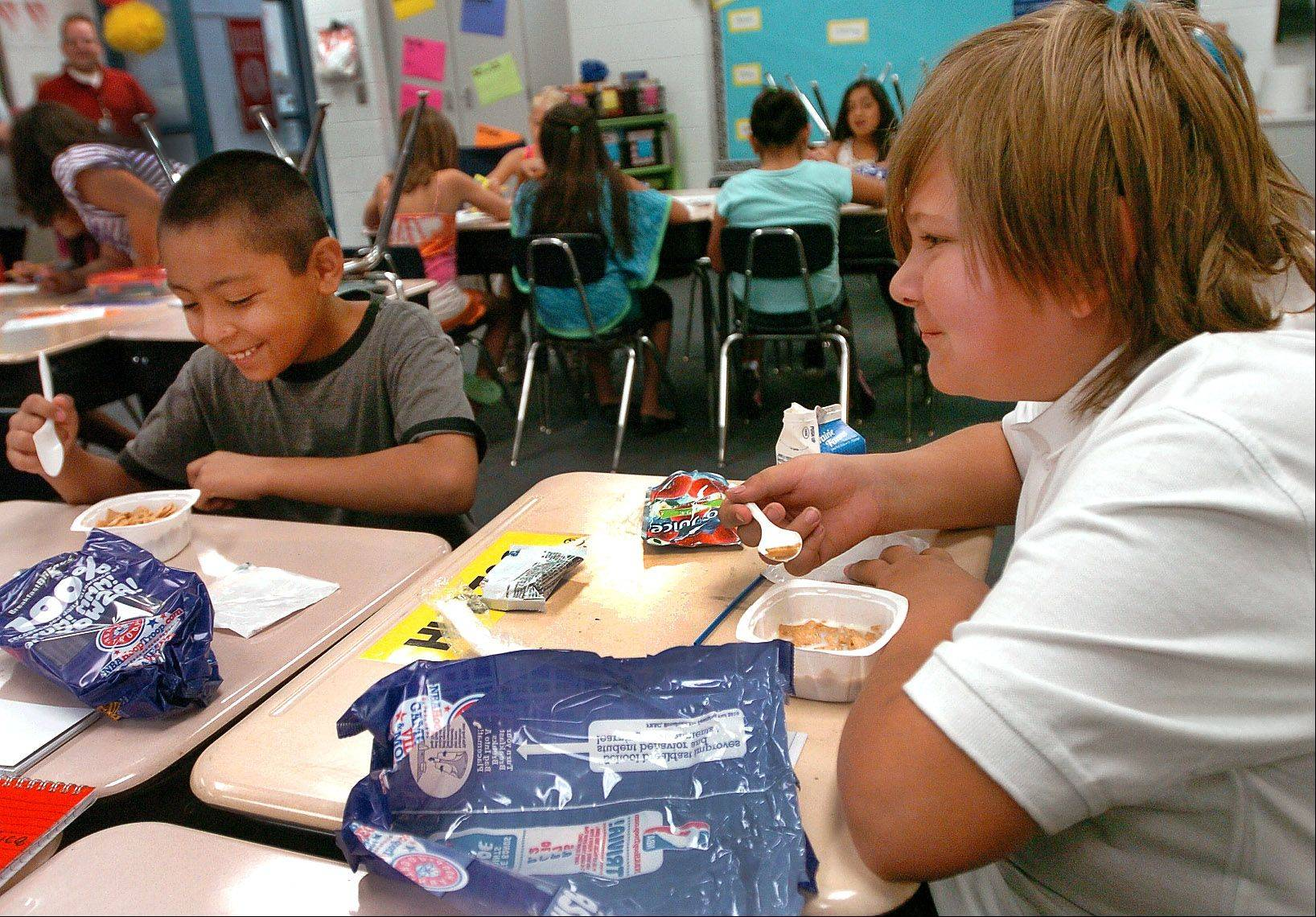 Hunter Watson, right, and Victor Lizardo, have breakfast at their desks at Jane Addams Elementary School in Palatine as part of the new universal free breakfast program.