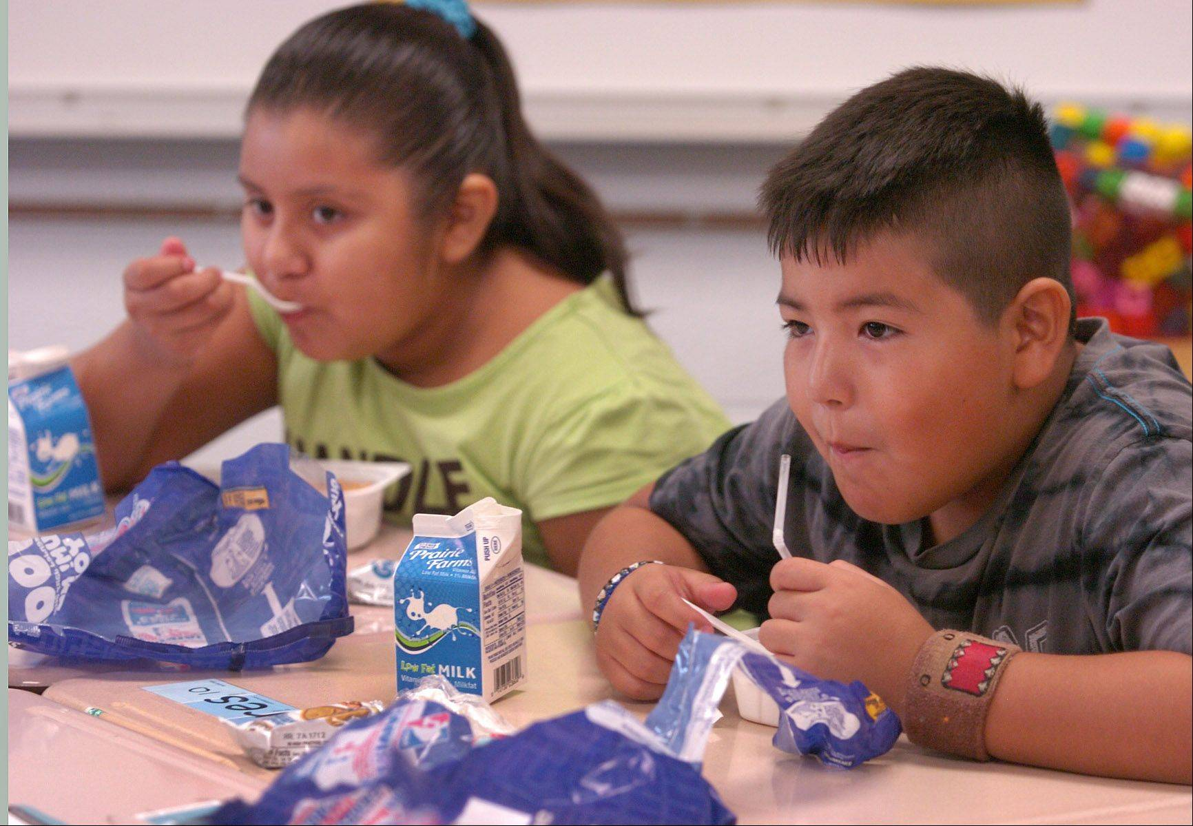 Fourth graders Lysandra Colin, left, and Andres Garcia take part in a new universal free breakfast program being piloted at Jane Addams Elementary School in Palatine.