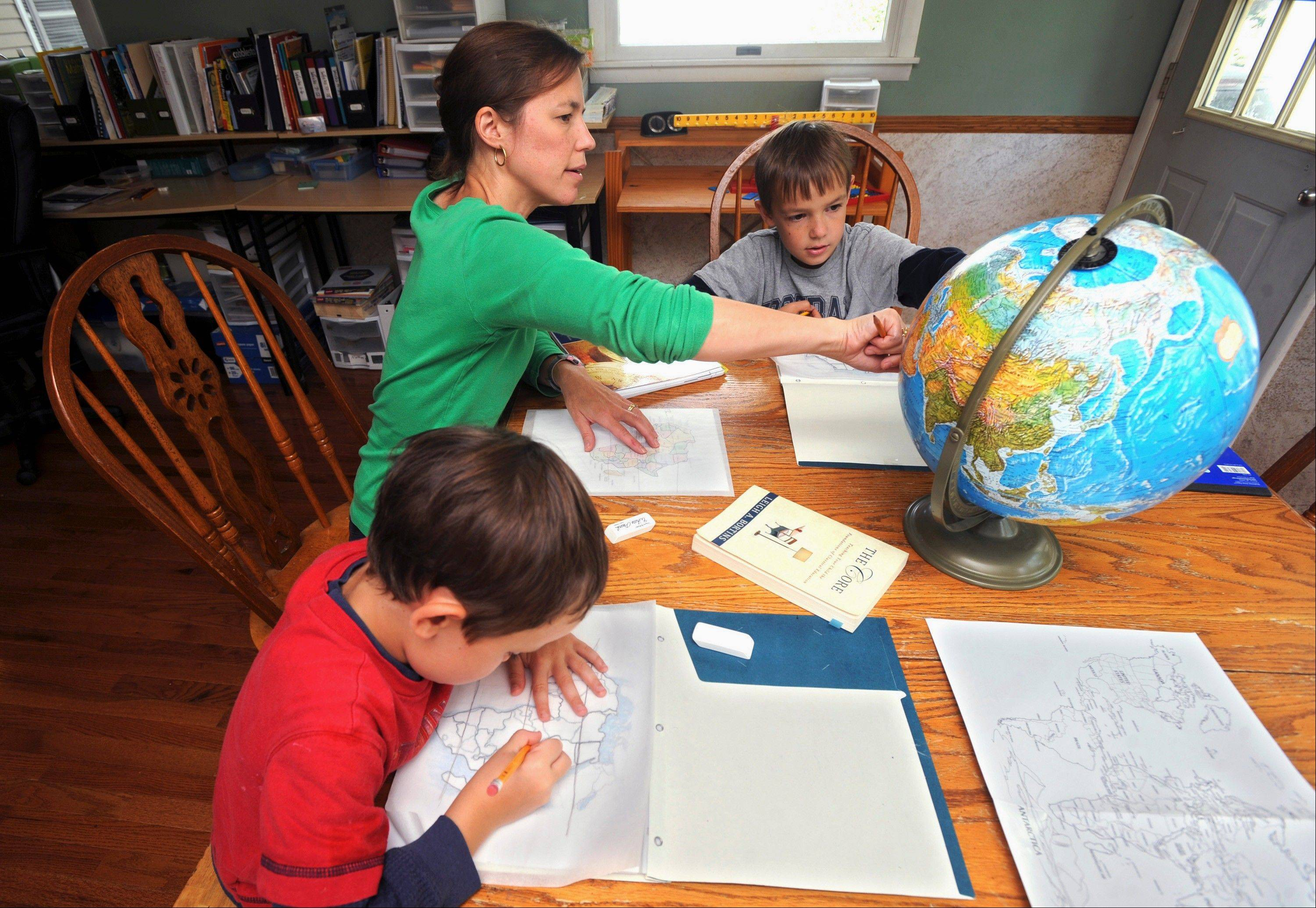 Elizabeth Boggs works with her sons Nathan, right, and Luke, left, with mapping and geography at her home in Charleston, Ill. Boggs is a member of the East Central Illinois Home Educators Network, a home-school support group with more than 40 member families.