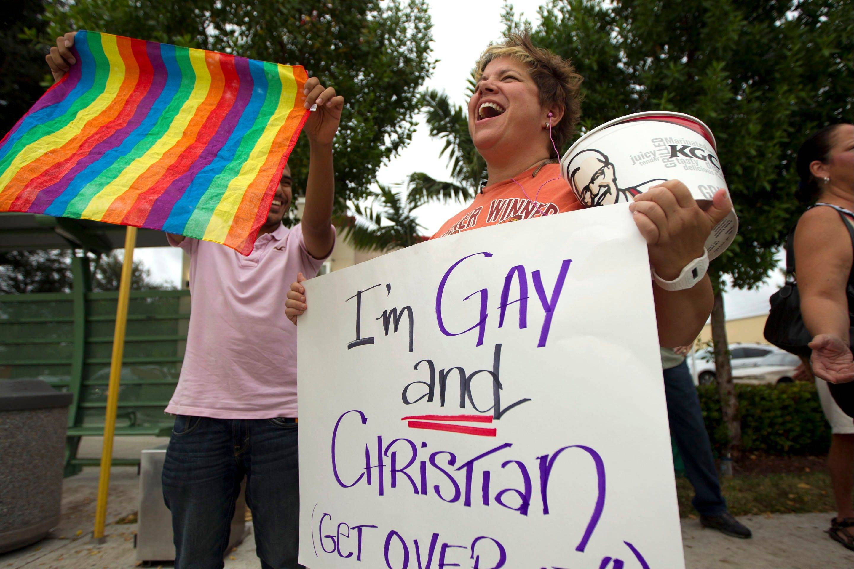 In a Friday, Aug. 3, 2012 file photo, Carri Jo Anderson holds a bucket of Kuntucky Fried Chicken and a gay pride sign as she joins the protest in front of a Chick-fil-A restaurant in Pompano Beach, Fla. Gay rights activists kissed at Chick-fil-A stores across the U.S. on Friday, just days after the company set a sales record when customers flocked to the restaurants to show support for the fast-food chain president's opposition to gay marriage. On this and so many other issues this election year, it seems harder to find that middle-ground gray when our debates seem so very black or white.